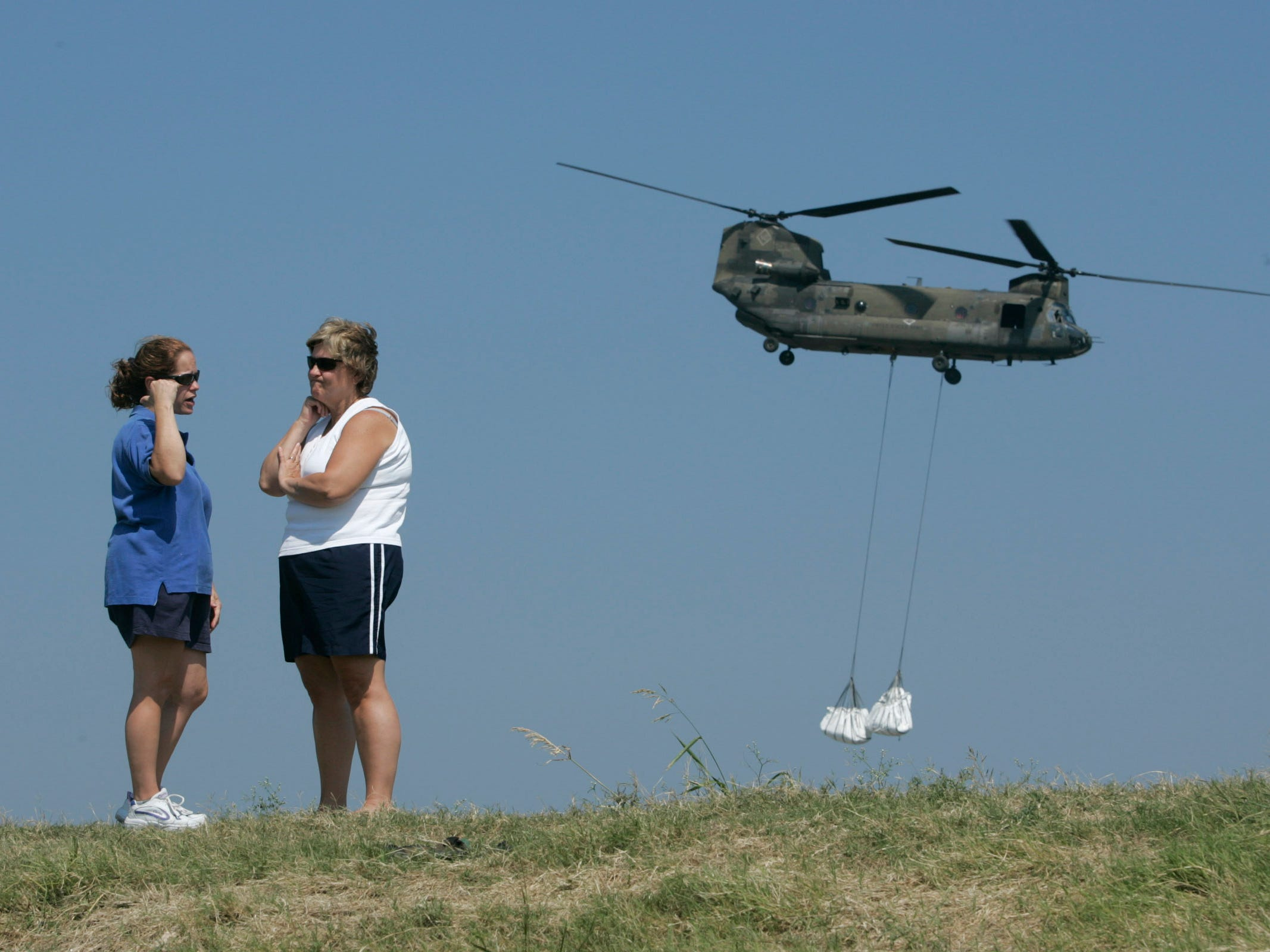 Army National Guard Chinook helicopters lift sand bags from a staging area near the 17th Street Canal levee collapse to airlift to other levee breeches on Tuesday, Sept. 6, 2005, in New Orleans after Hurricane Katrina.
