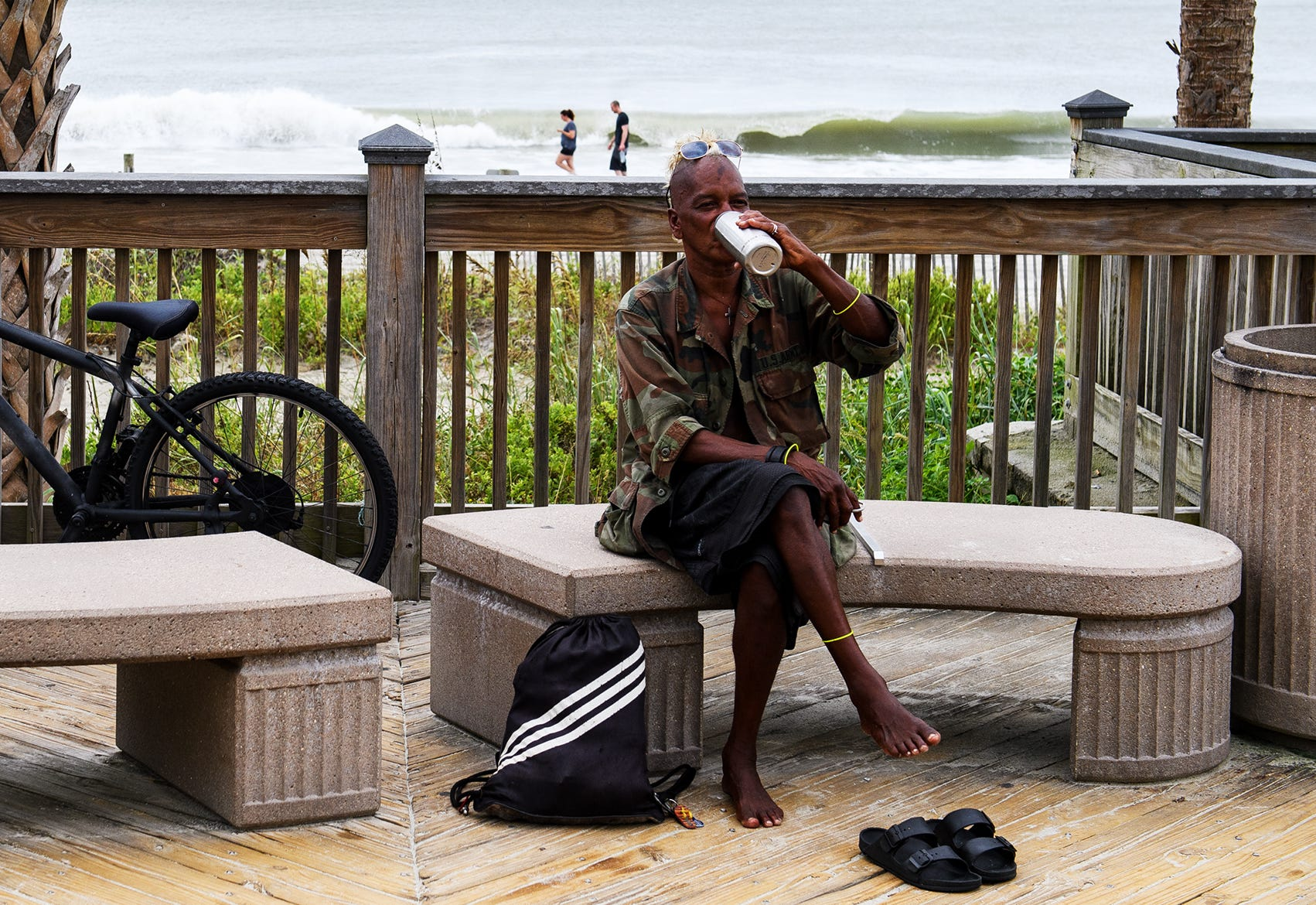 """Shane """"Rooster"""" Bacchus, a homeless man living in Myrtle Beach, S.C., takes a drink from his water bottle at the Myrtle Beach Boardwalk and Promenade on Sept. 13, 2018. Bacchus said he will be sleeping in a truck during Hurricane Florence."""
