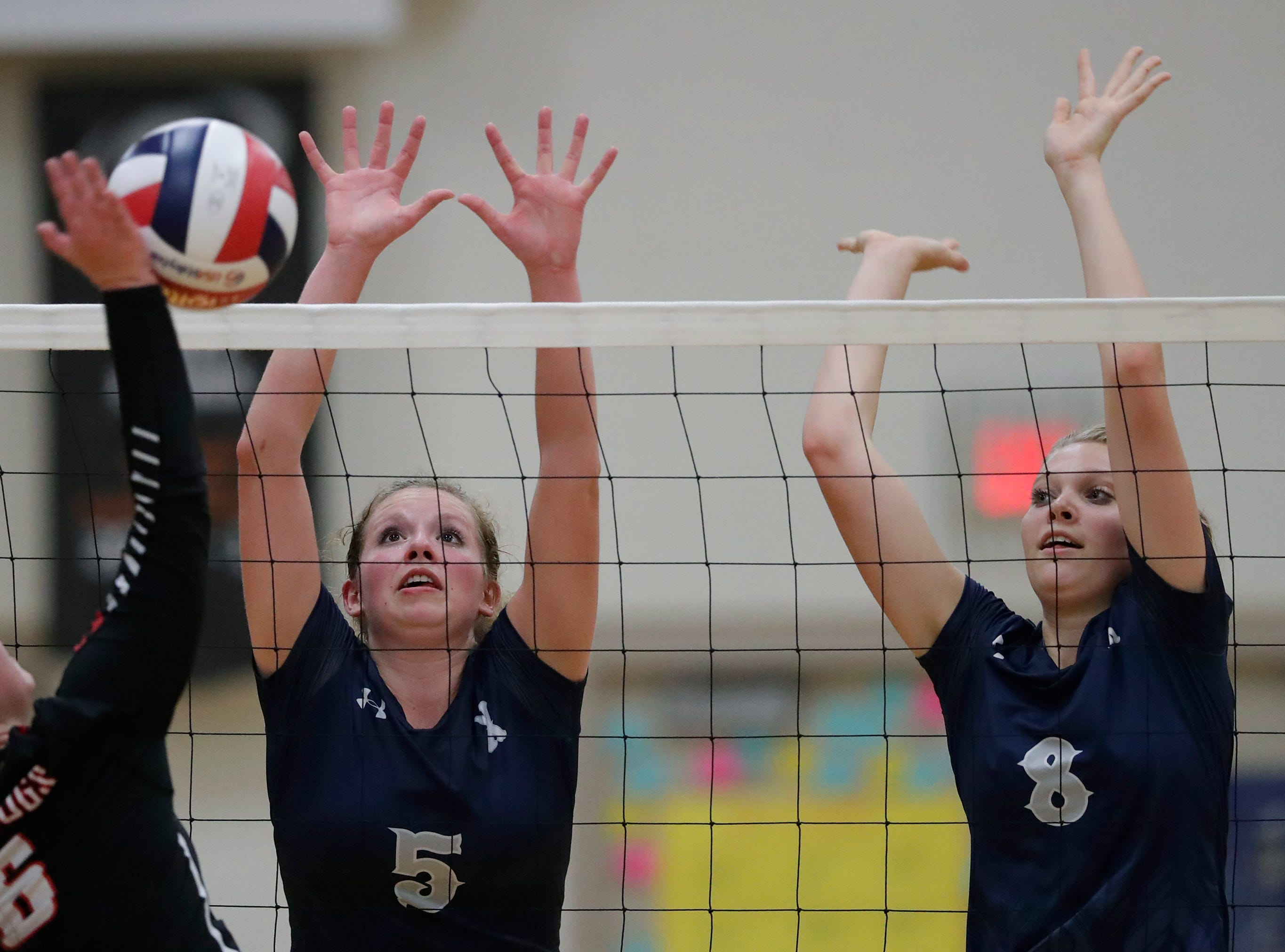 Xavier High School's Emma Vosters (5) and Morgan Michalkiewicz (8) block against New London High School's Megan Millard (6) during their girls volleyball match Thursday, Sept. 13, 2018, in Appleton, Wis. 