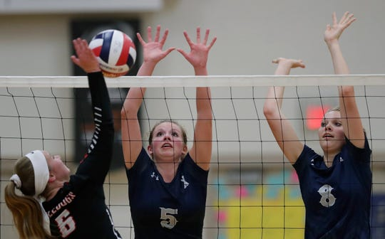 Xavier's Emma Vosters (5) and Morgan Michalkiewicz (8) make a block against New London's Megan Millard (6) during their volleyball match Sept. 13 in Appleton.