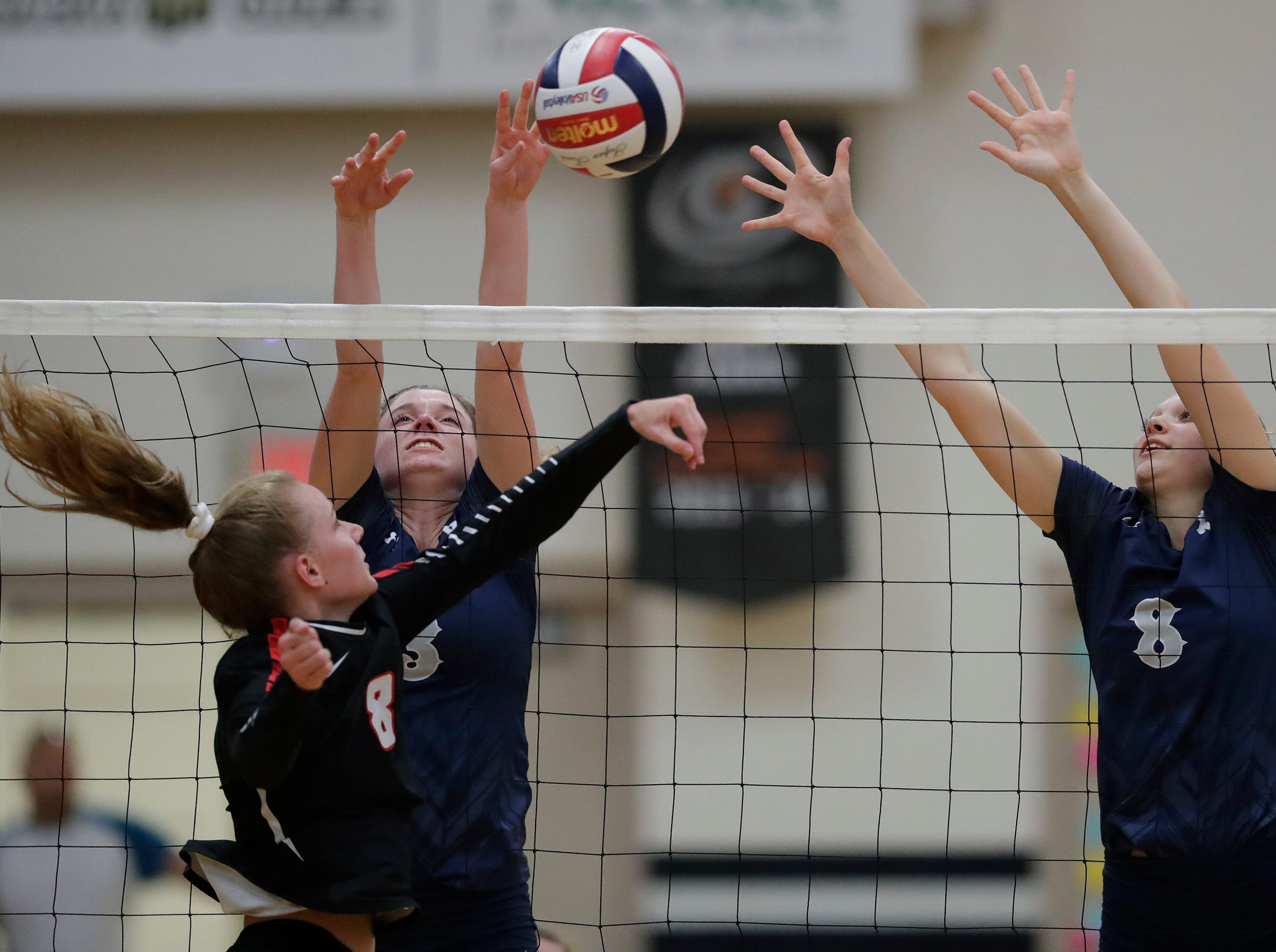 Xavier High School's Kaitlyn Tetzlaff (3) and Morgan Michalkiewicz (8) block against New London High School's Lauren Stroesenreuther (8) during their girls volleyball match Thursday, Sept. 13, 2018, in Appleton, Wis. 
