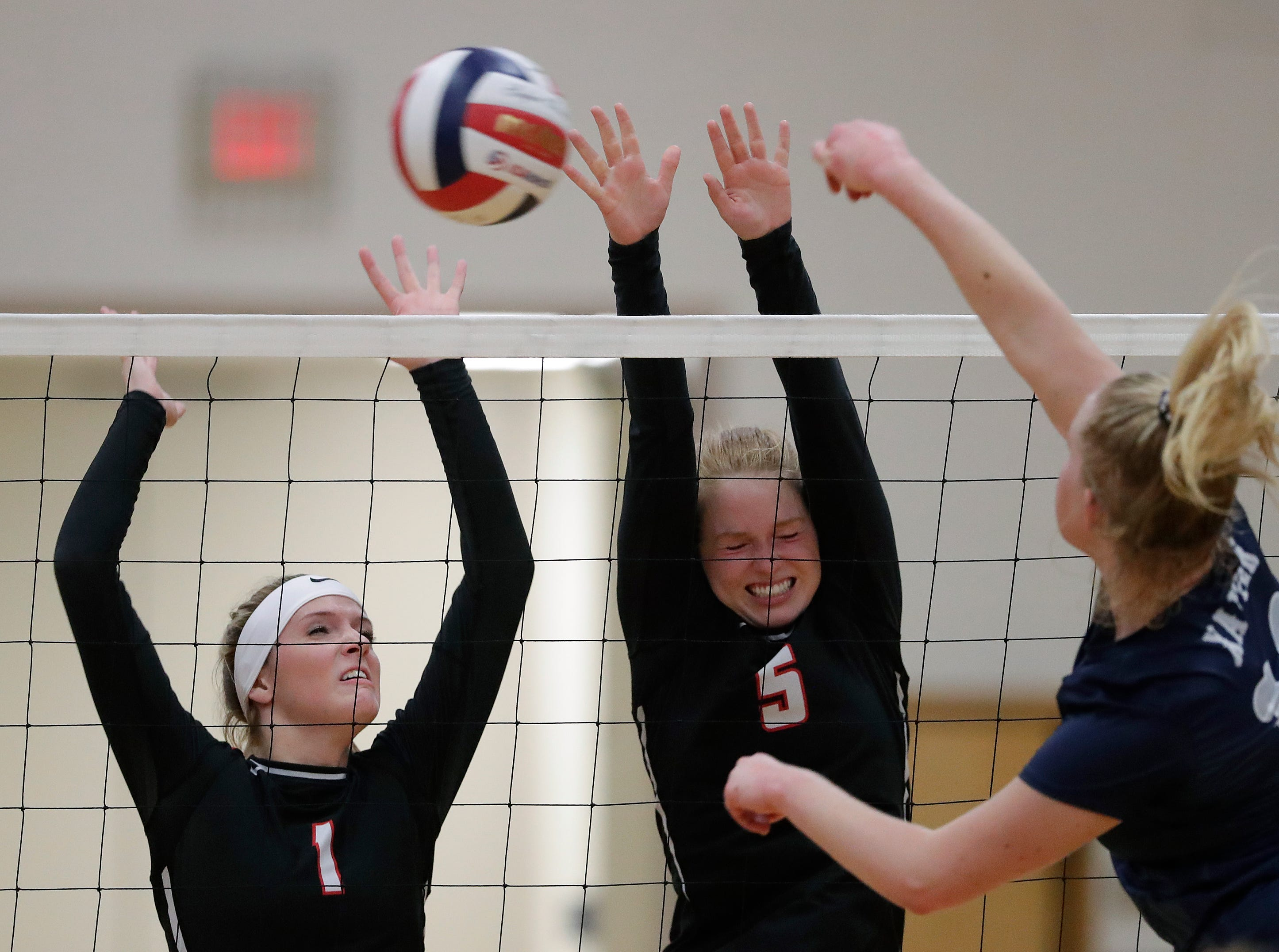 New London High School's Marissa Messina (1) and Abbi Gillespie (5) block against Xavier High School's Emma Oelhafen (10) during their girls volleyball match Thursday, Sept. 13, 2018, in Appleton, Wis. 