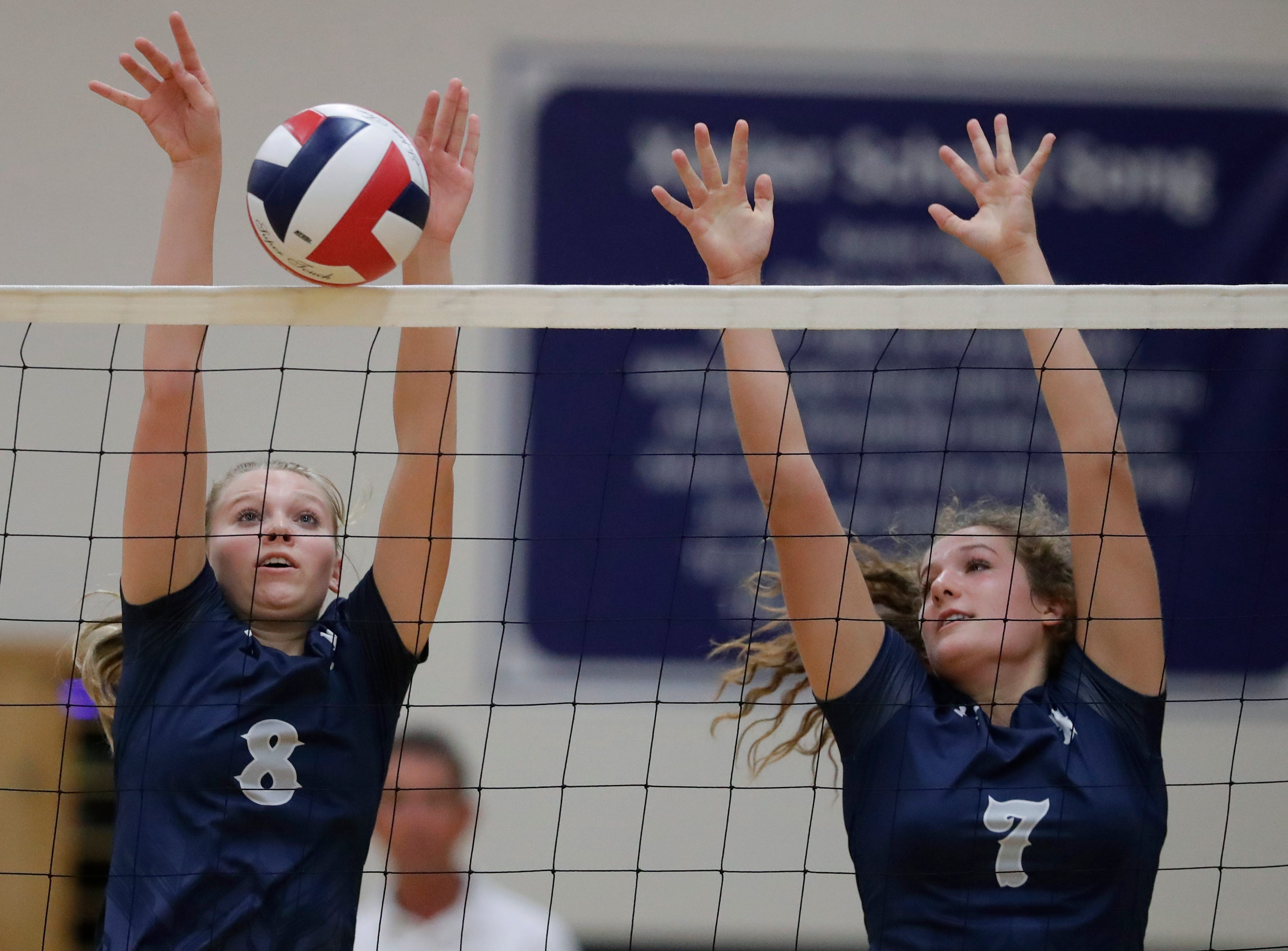 Xavier High School's Morgan Michalkiewicz (8) and Anna Hoerning (7) block against New London High School during their girls volleyball match Thursday, Sept. 13, 2018, in Appleton, Wis. 