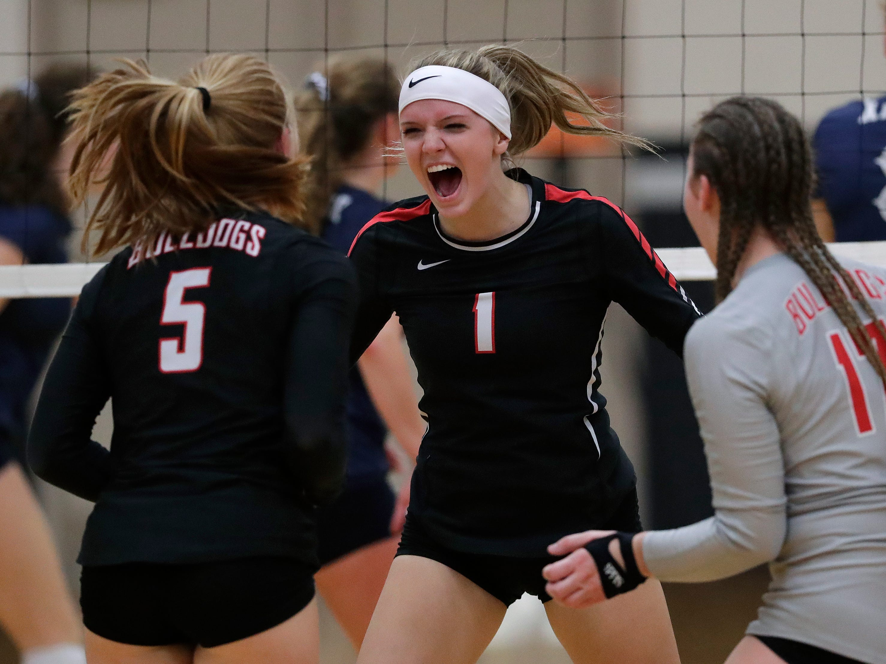 New London High School's Abbi Gillespie (5), Marissa Messina (1) and Emmea Blum (17) celebrate winning a point against Xavier High School during their girls volleyball match Thursday, Sept. 13, 2018, in Appleton, Wis. 