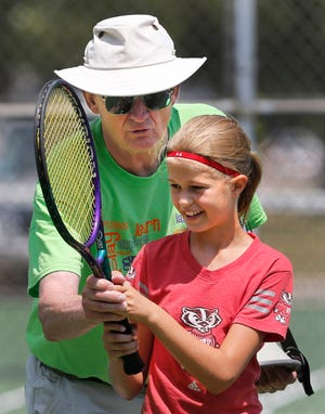Tom Berven teaches Kaylin Roth how to volley at the net during a summer tennis program.