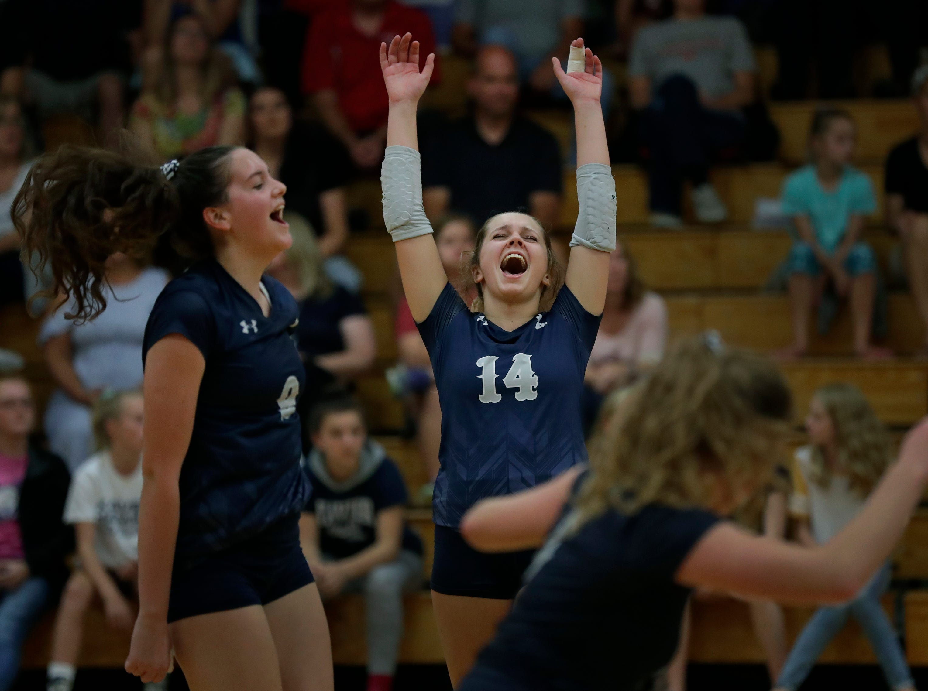 Xavier High School's Gabby Murray (9), Catherine Adair (14) and Emma Vosters (5) celebrate winning a point against New London High School during their girls volleyball match Thursday, Sept. 13, 2018, in Appleton, Wis. 