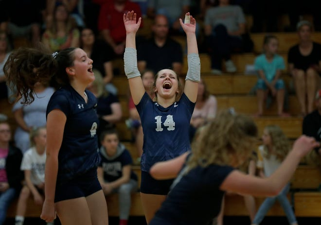 Xavier's Gabby Murray (9), Catherine Adair (14) and Emma Vosters (5) celebrate a point against New London on Sept. 13. Xavier plays top-ranked Little Chute in a WIAA Division 2 sectional semifinal Thursday in Chilton.