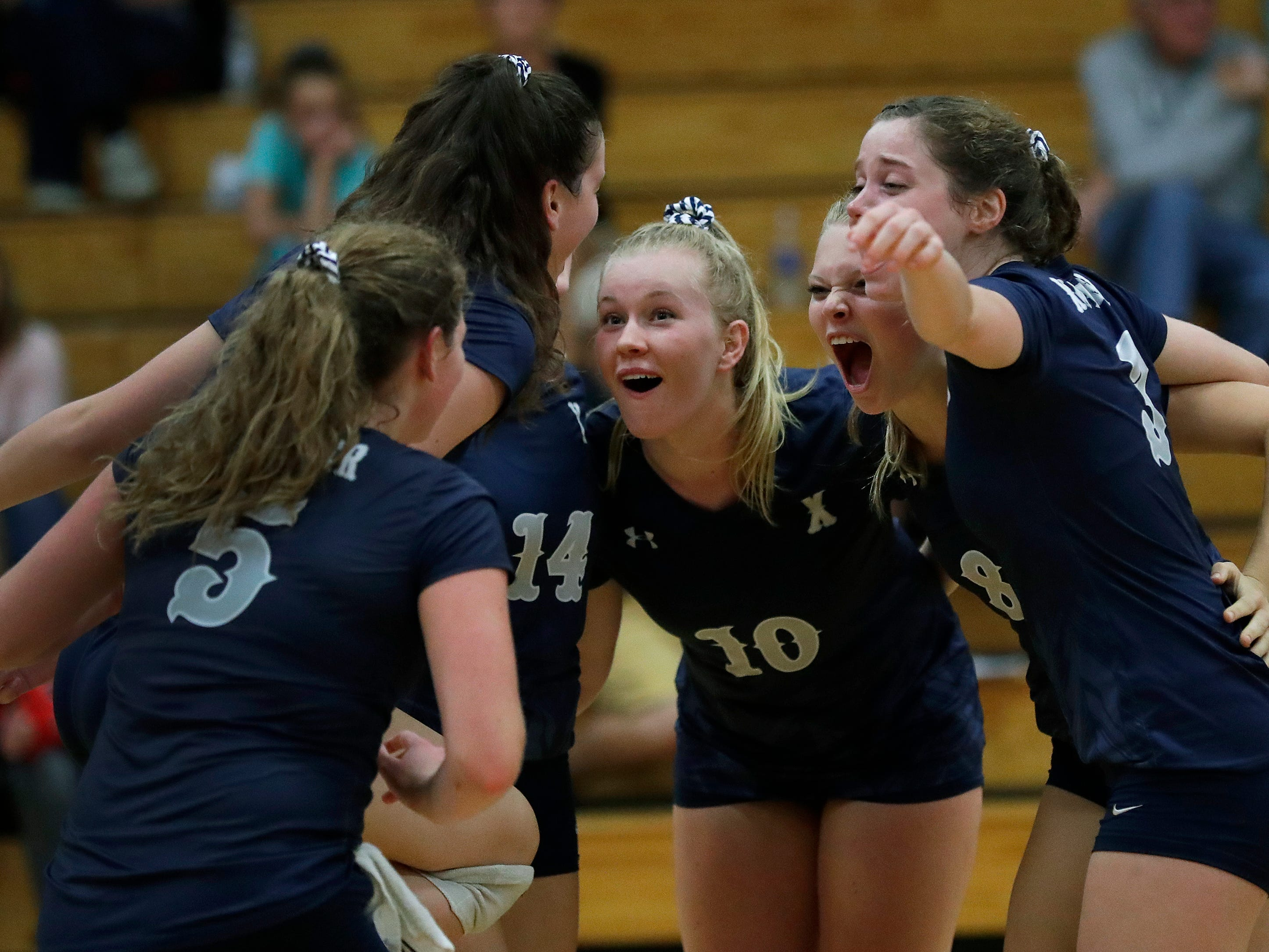 Xavier High School's players celebrate winning a point against New London High School during their girls volleyball match Thursday, Sept. 13, 2018, in Appleton, Wis. 