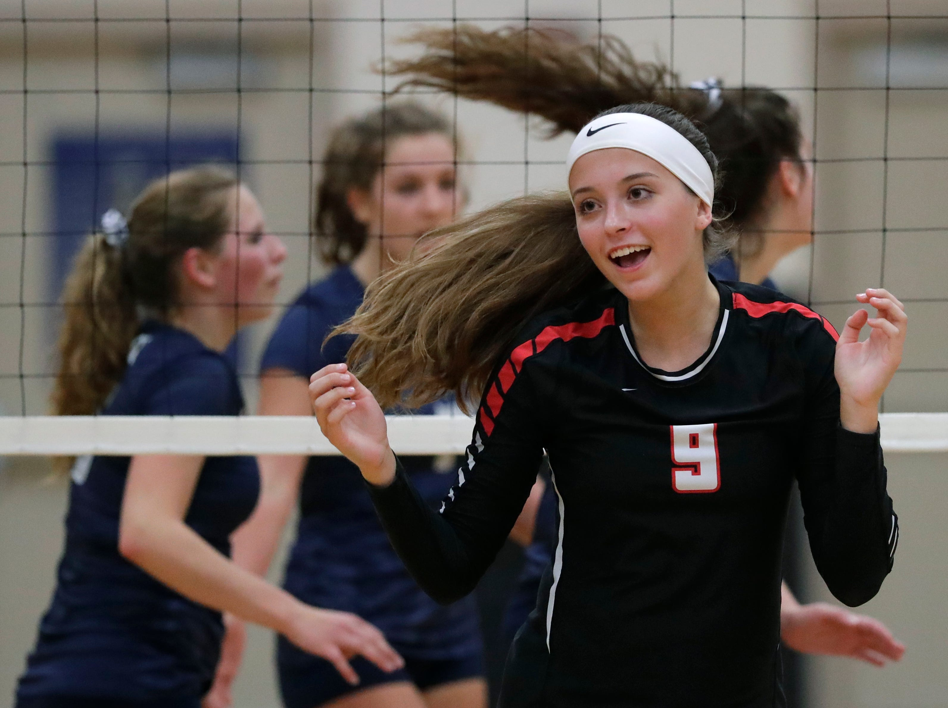New London High School's Mackenzie Fischer (9) celebrates winning a point against Xavier High School during their girls volleyball match Thursday, Sept. 13, 2018, in Appleton, Wis. 