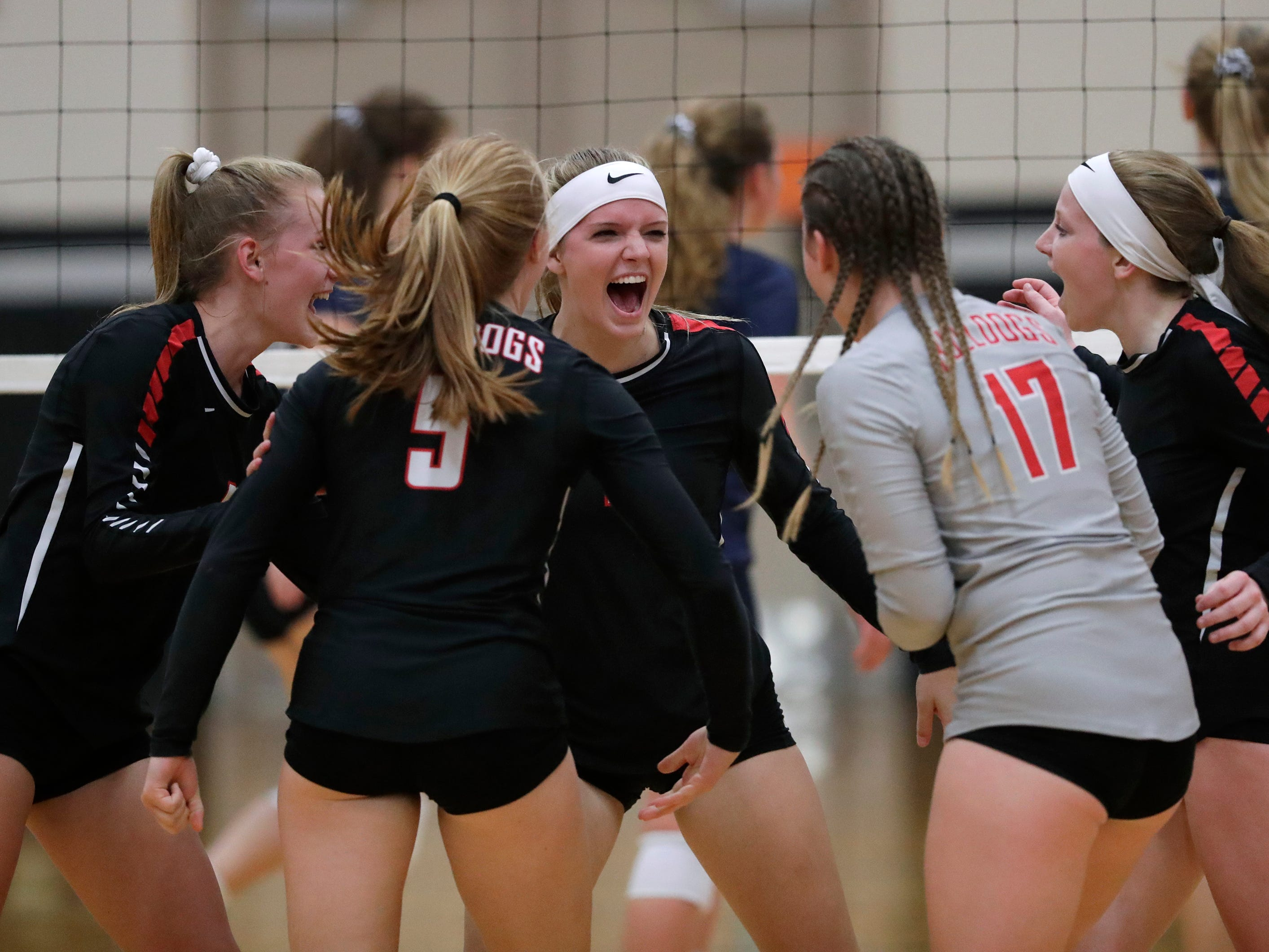 New London High School's players celebrate winning a point against Xavier High School during their girls volleyball match Thursday, Sept. 13, 2018, in Appleton, Wis. 
