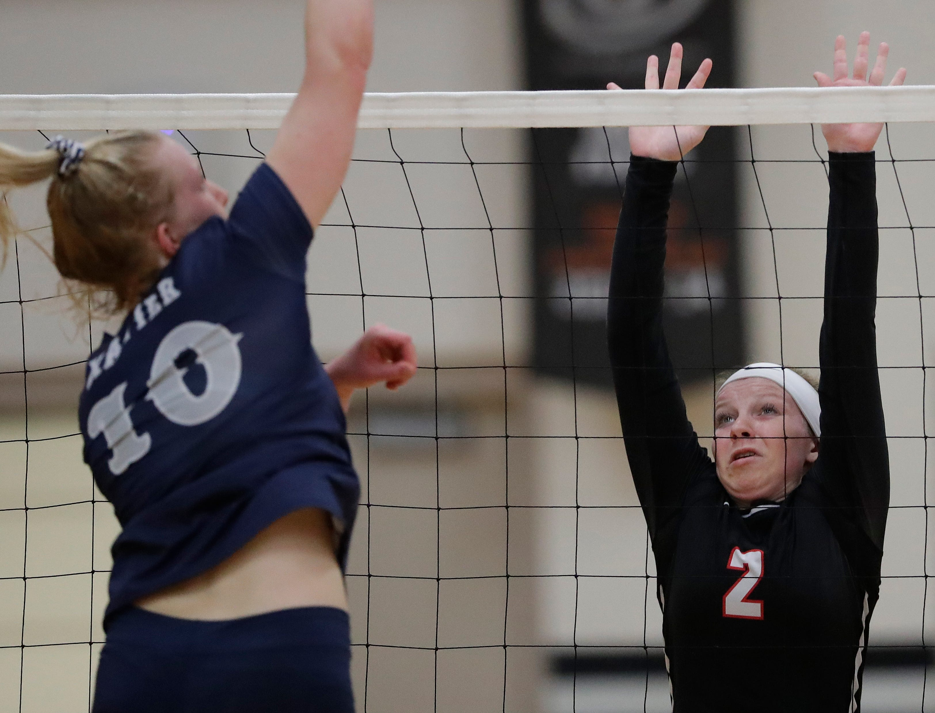 New London High School's Jessica Halvorson (2) blocks against Xavier High School's Emma Oelhafen (10) during their girls volleyball match Thursday, Sept. 13, 2018, in Appleton, Wis. 