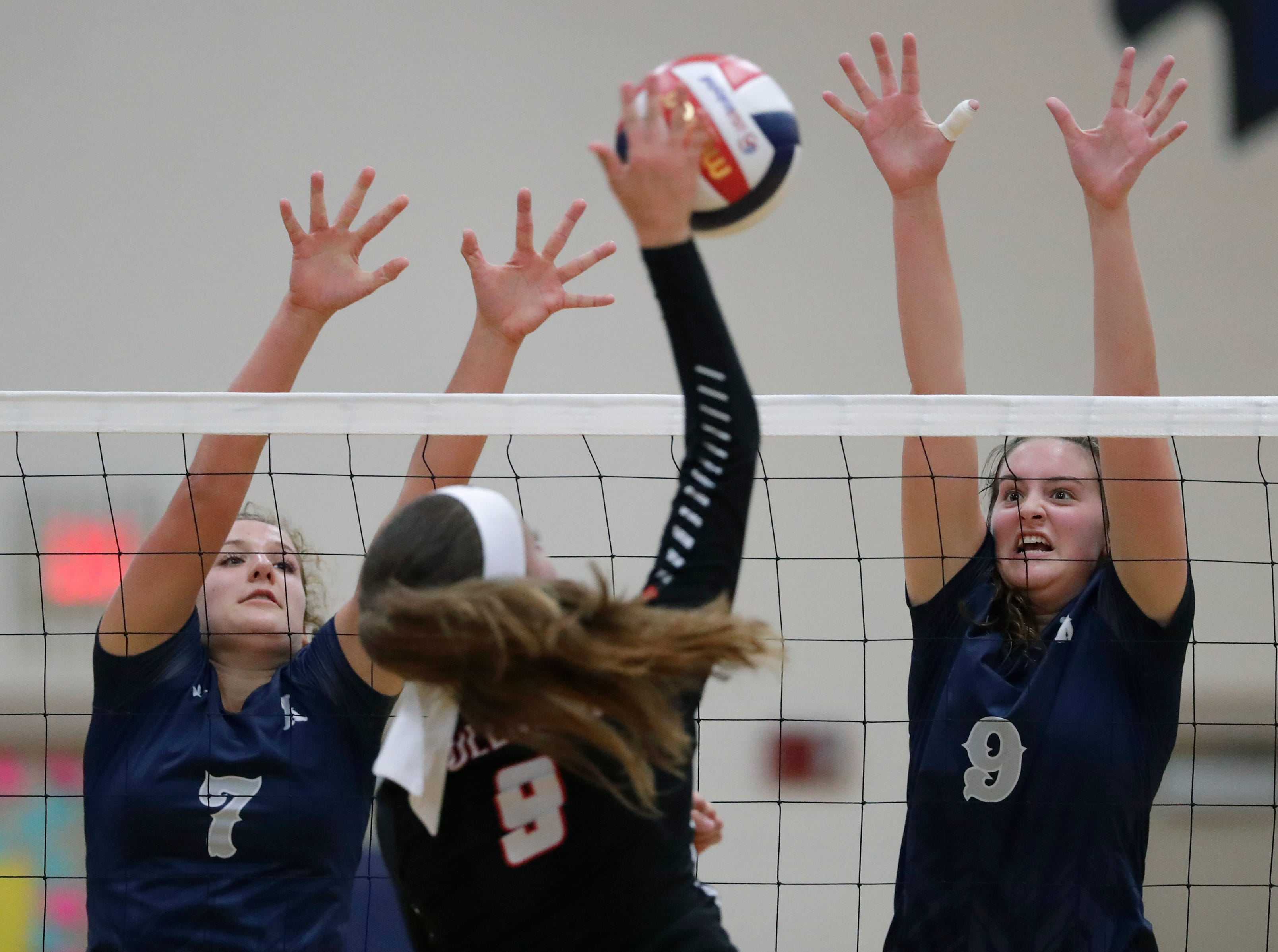Xavier High School's Anna Hoerning (7) and Gabby Murray (9) block against New London High School's Mackenzie Fischer (9) during their girls volleyball match Thursday, Sept. 13, 2018, in Appleton, Wis. 