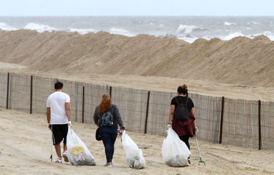 People clean debris off the beach Friday morning, September 14, 2018, past dunes created to keep ocean waves off the Belmar beach.