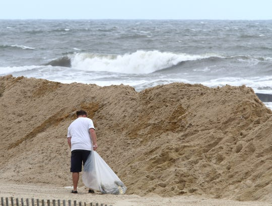 A man cleans debris off the beach Friday morning, September 14, 2018, past dunes created to keep ocean waves off the Belmar beach.