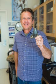 Martin Becker, a paleontologist at William Patterson University holds the fossil tooth of a megalodon.