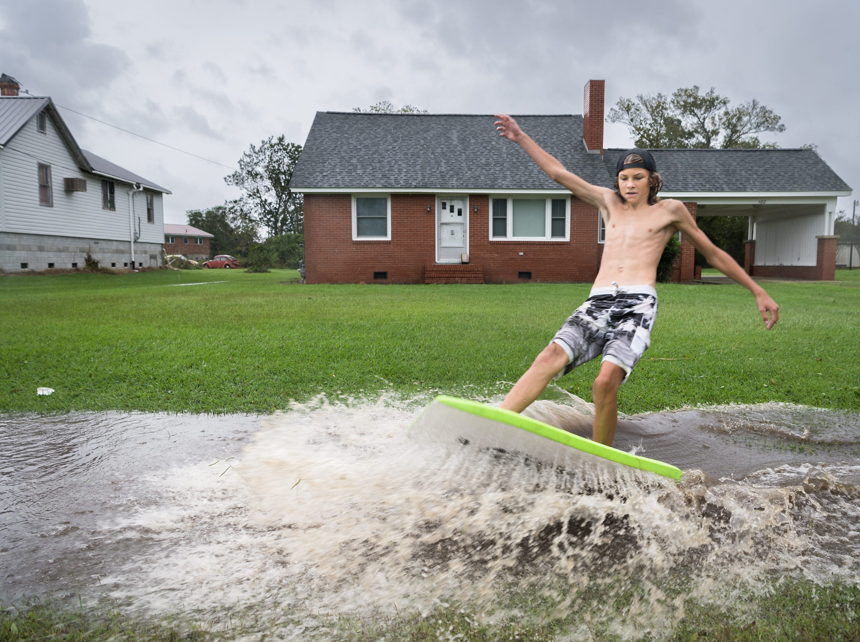 Deacon Etheredge, 14, surfs on a large puddle on Main Street in Swan Quarter, N.C Sept. 14, 2018, after Hurricane Florence made landfall.