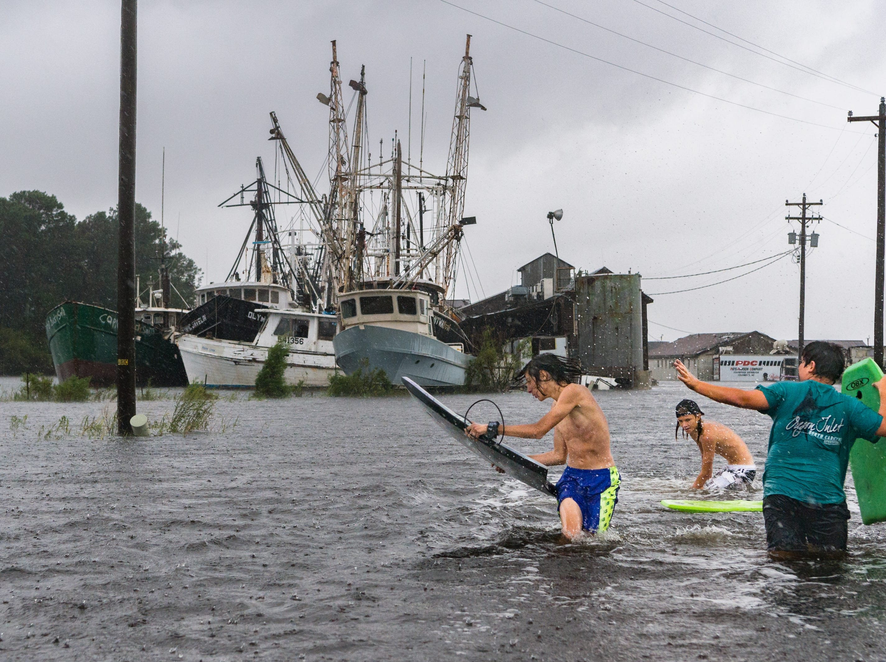 Fortino Beltran, Deacon Etheredge, and Dustin Briggs, all 14, surf through the flooded Swan Quarter, N.C harbor at the Swan Quarter Bay Sept. 14, 2018, after Hurricane Florence made landfall.