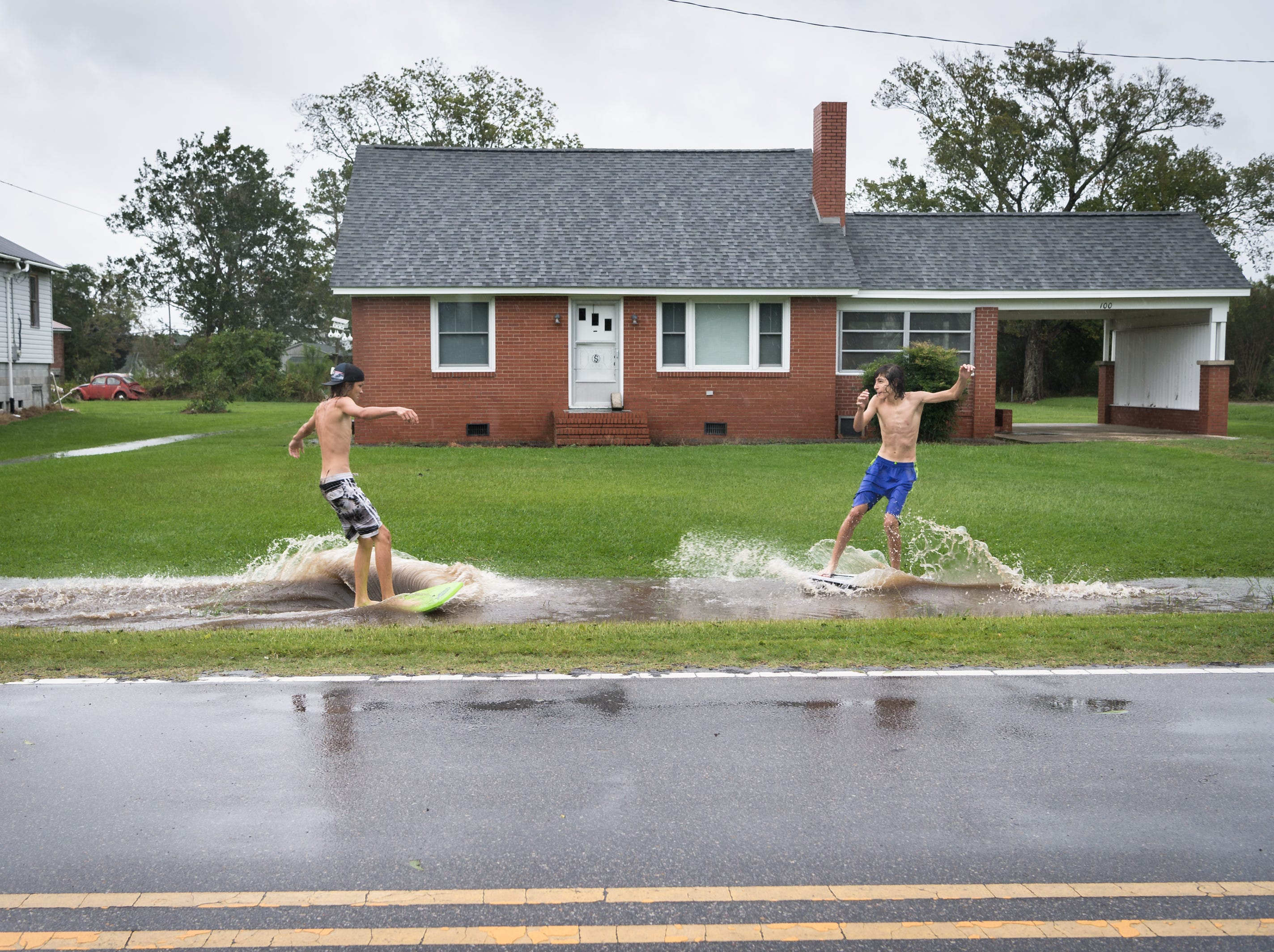 Deacon Etheredge, 14, and Fortino Beltran, also 14, surf on a large puddle on Main Street in Swan Quarter, N.C Sept. 14, 2018, after Hurricane Florence made landfall.