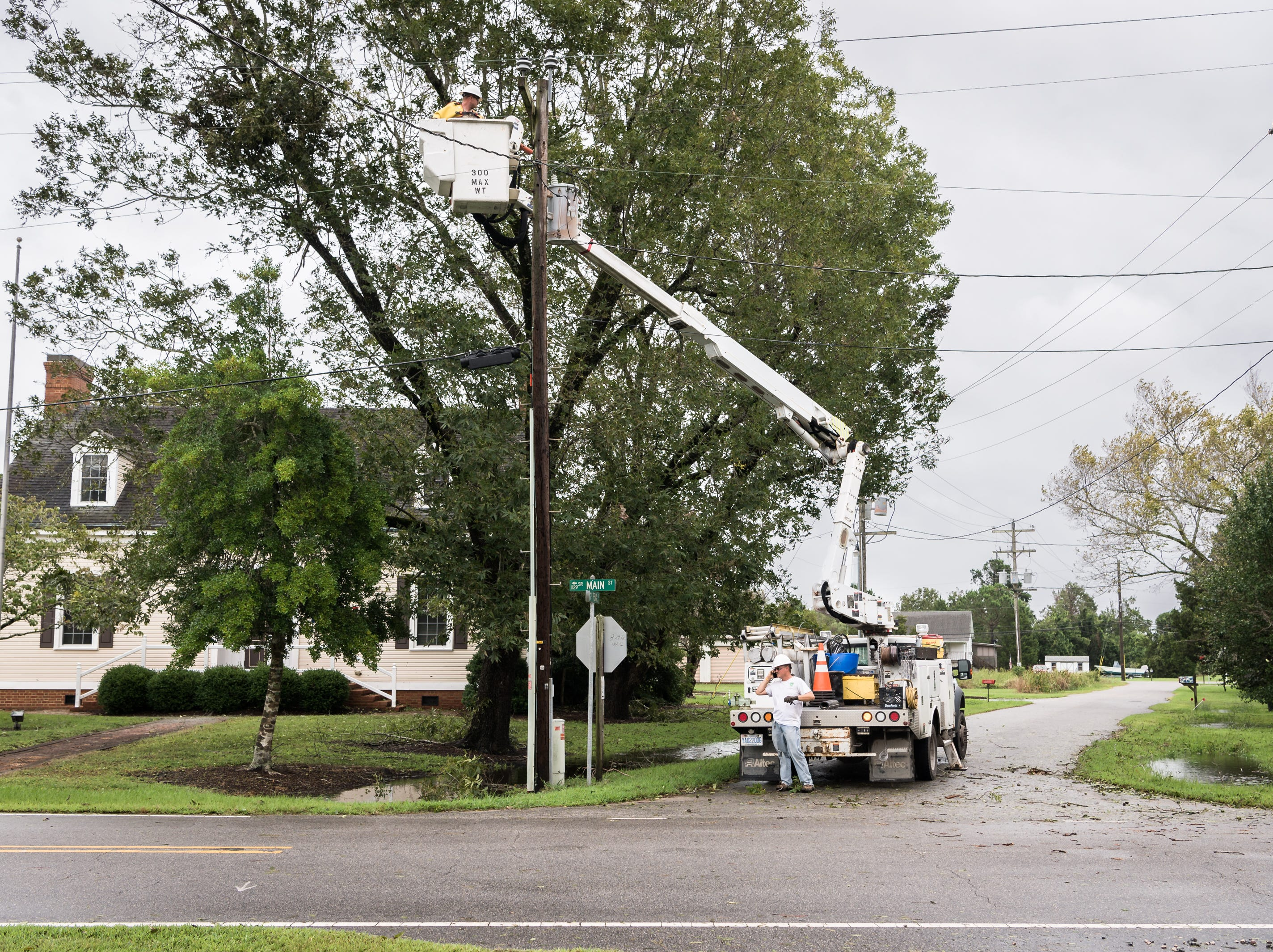 Utility workers from Tideland EMC make a repair to a utility pole on Main Street in Swan Quarter, N.C Sept. 14, 2018, after Hurricane Florence made landfall in Wilmington, N.C.