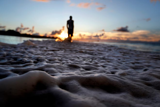 The surf washes up the shore at low tide as Andrew Lingle walks along the beach as Hurricane Florence approaches the east coast in Atlantic Beach Wednesday.