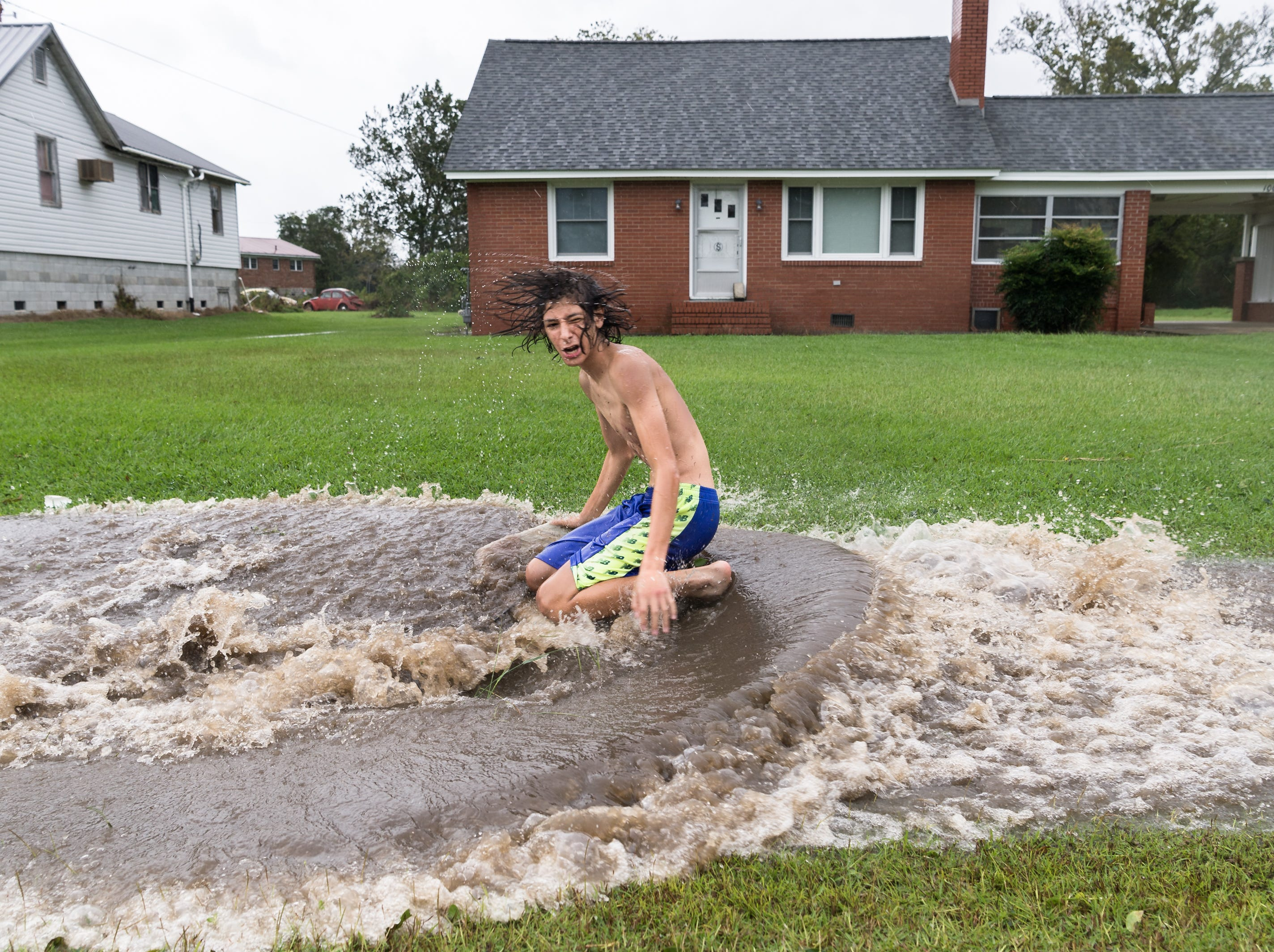 Fortino Beltran, 14, splashes into a large puddle while surfing on Main Street in Swan Quarter, N.C Sept. 14, 2018, after Hurricane Florence made landfall.