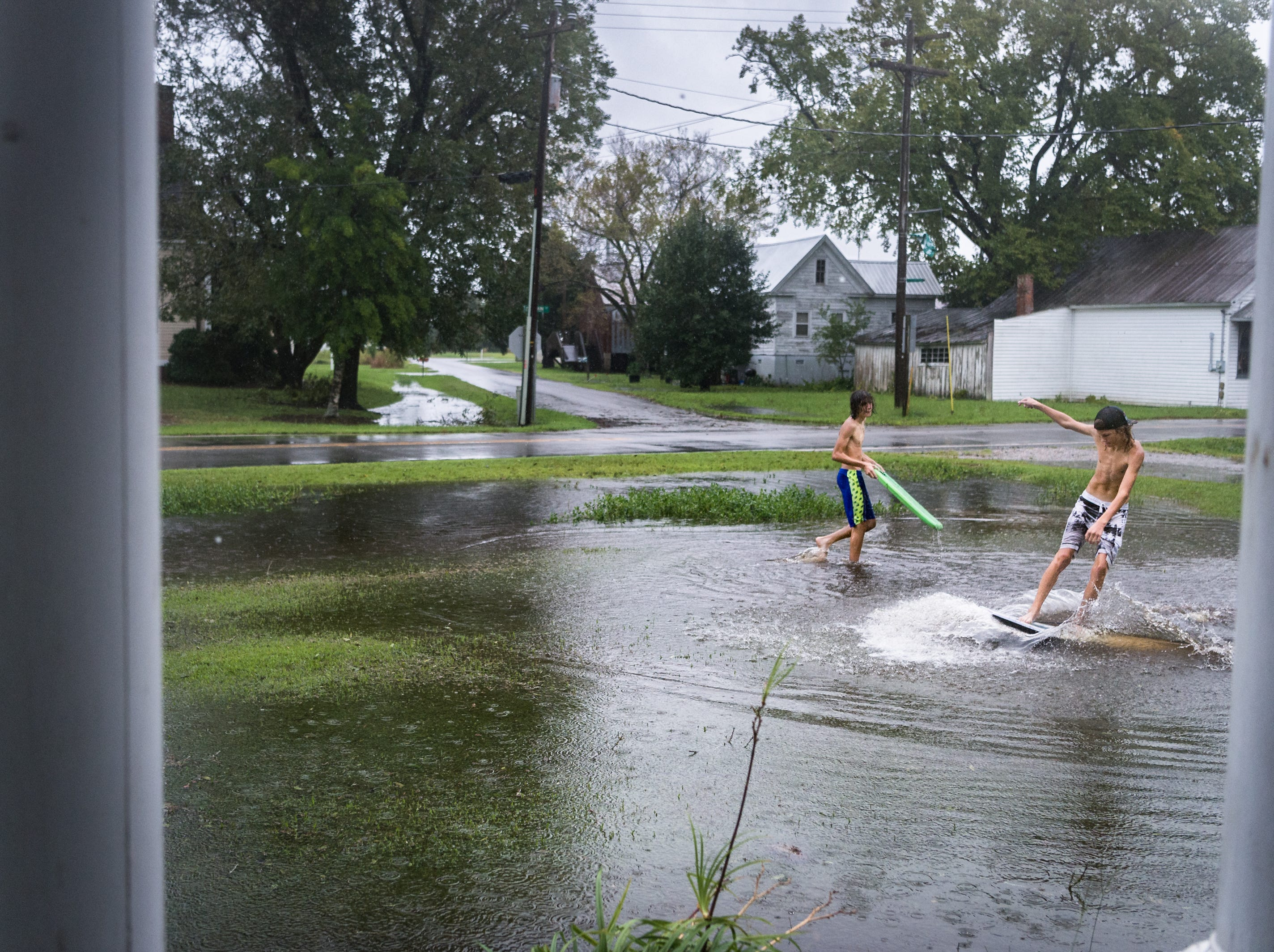 Fortino Beltran, 14 and Deacon Etheredge, also 14, surf on a large puddle in a front yard on Main Street in Swan Quarter, N.C Sept. 14, 2018, after Hurricane Florence made landfall.