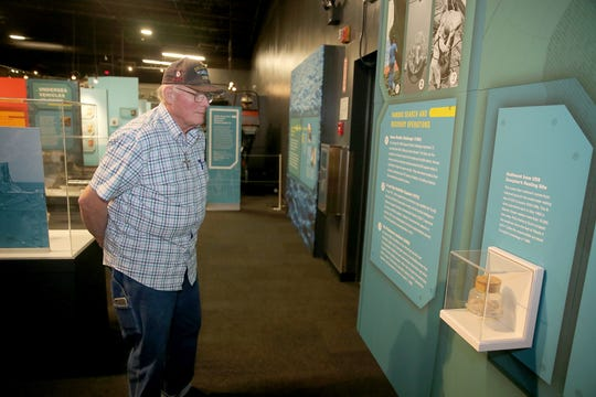 Volunteer Harry Gilger, a Navy submarine veteran, views for the first time the new exhibit at the Keyport Naval Undersea Museum. On the right is a vase with sediment from the resting site of the USS Scorpion, which sank in 1968.