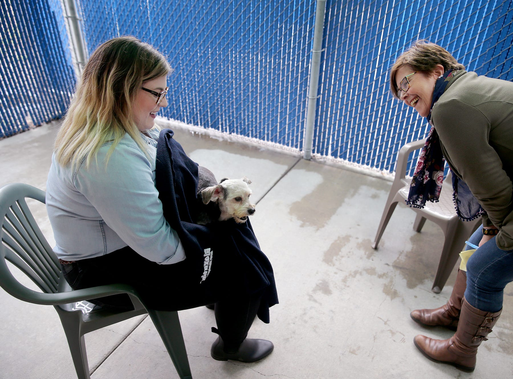 Samantha Fairweather, left, the assistant director of animal welfare holds Chestnut as Rhonda Manville the marketing director talks to him at the Kitsap Humane Society feeds some of the twenty six dogs are at the Kitsap Humane Society after being rescued from a home in Chico.
