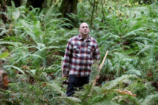 Camp Indianola Director Darin Gemmer looks around a camp trail that is carpeted with ferns.