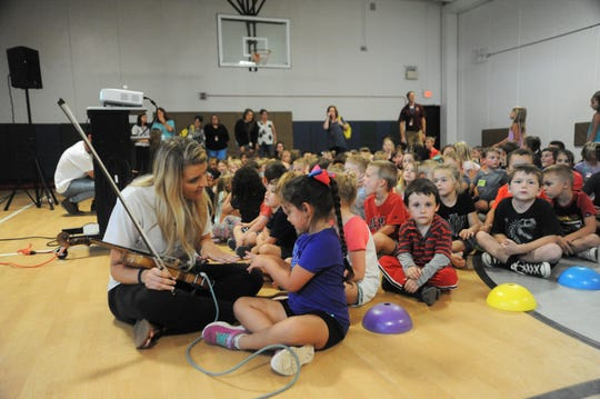 Summer McMahan of Summer Brooke and the Mountain Faith Band, chats with a student at Black Mountain Primary before performing for at the school.