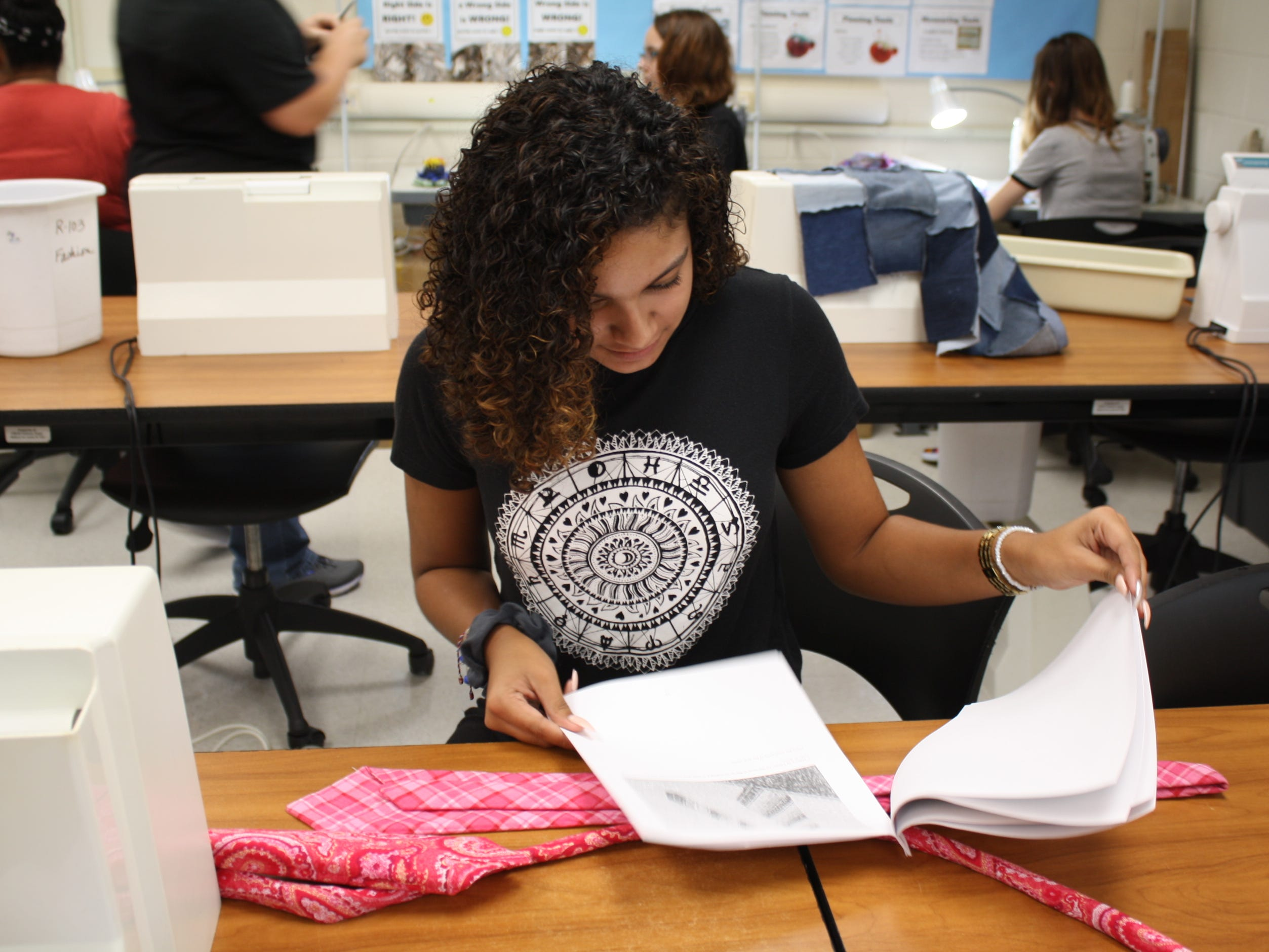 Destanie Genao, a senior at Palm Bay High School, puts the finishing touches on her plaid pink tie. She and other fashion design students at Brevard County high schools are making custom ties for Superintendent Mullins to wear during Breast Cancer Awareness Month.
