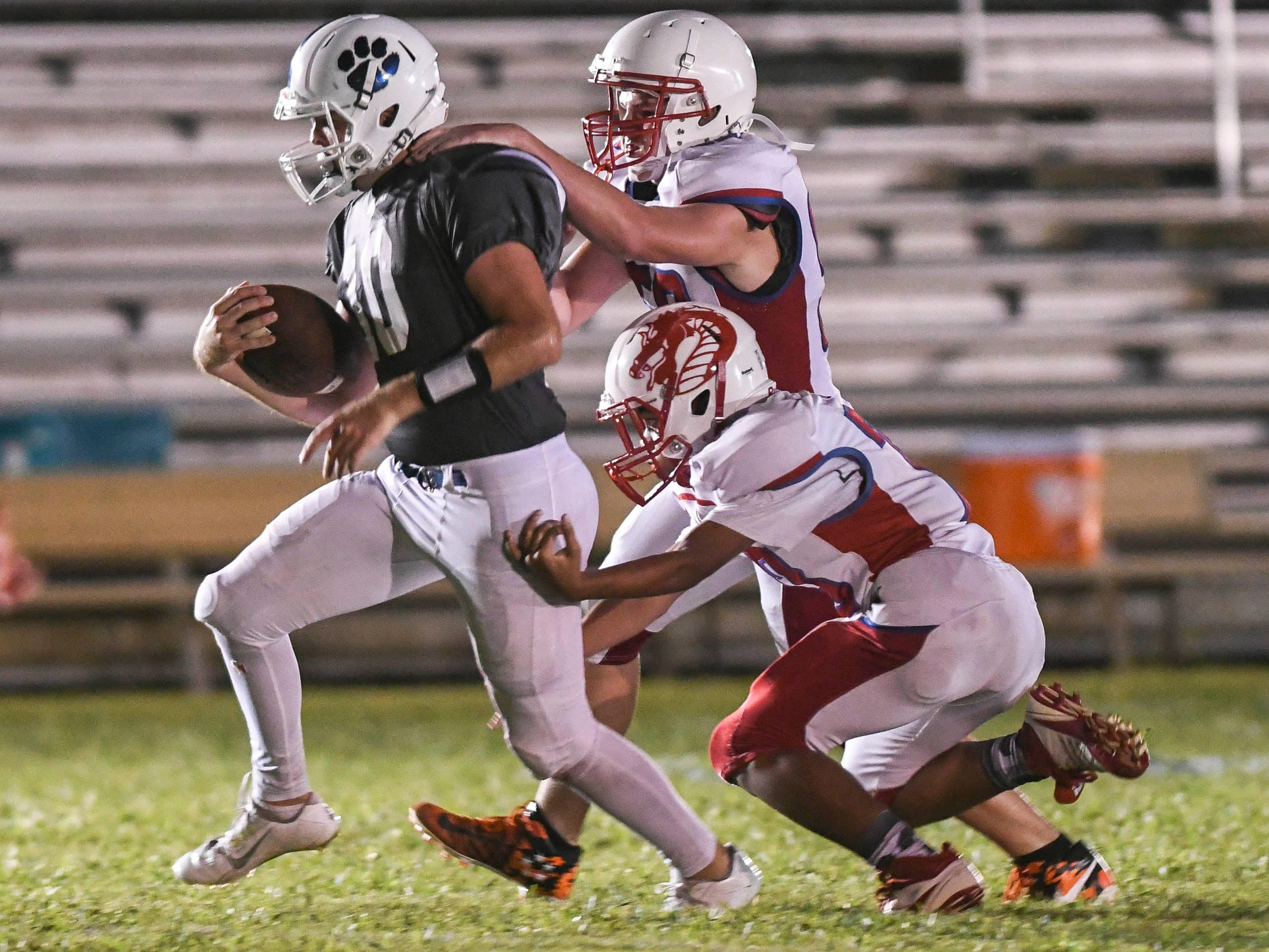 Merritt Island Christian QB Carson Brogdon is dragged down by Garrett Hunt (50) and Malcolm Rosebud (73) of Florida School for the Dead during Thursday's game.