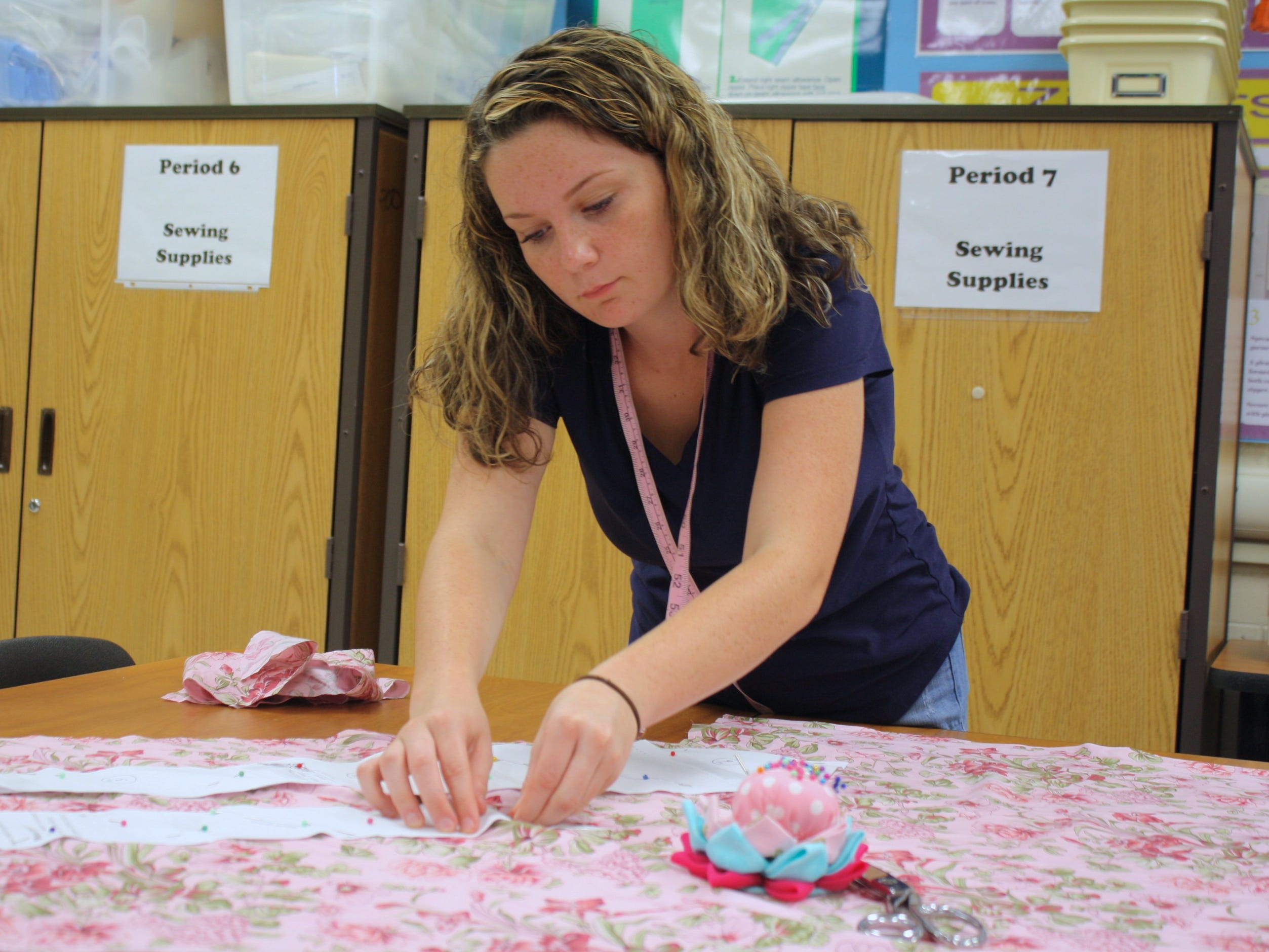 Patience Logsdon, a senior at Palm Bay High School, pins a tie pattern to a floral piece of fabric. She and other fashion design students at Brevard County high schools are making custom ties for Superintendent Mullins to wear during Breast Cancer Awareness Month.