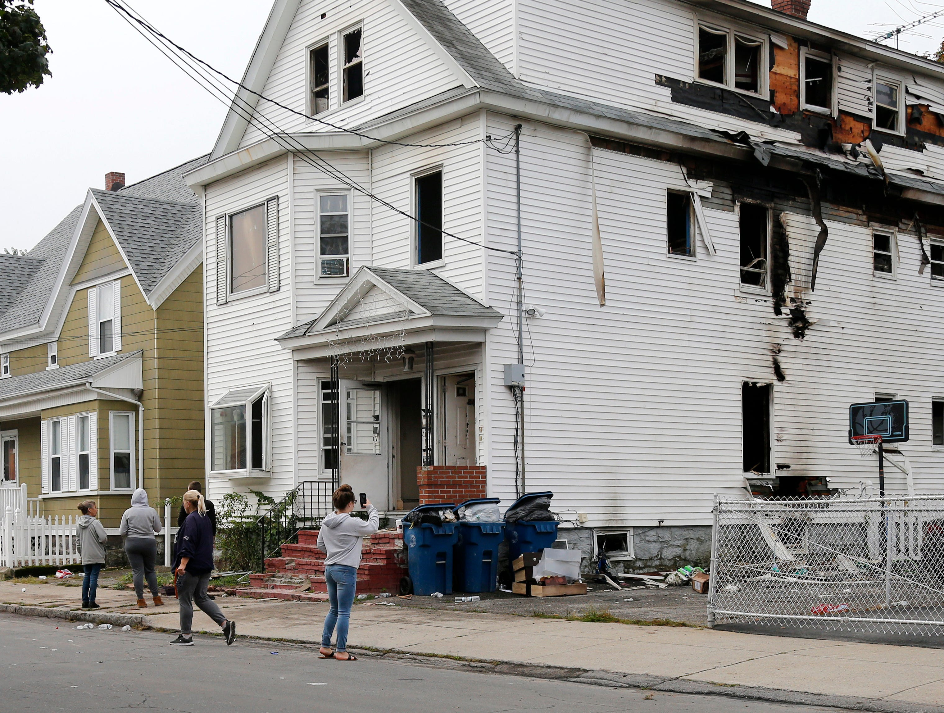 Lawrence residents stop to take photos of a house on Bowdoin Street in Lawrence Mass., Friday, Sept. 14, 2018. The home was one of multiple houses that went up in flames on Thursday afternoon after gas explosions and fires triggered by a problem with a gas line that feeds homes in several communities north of Boston