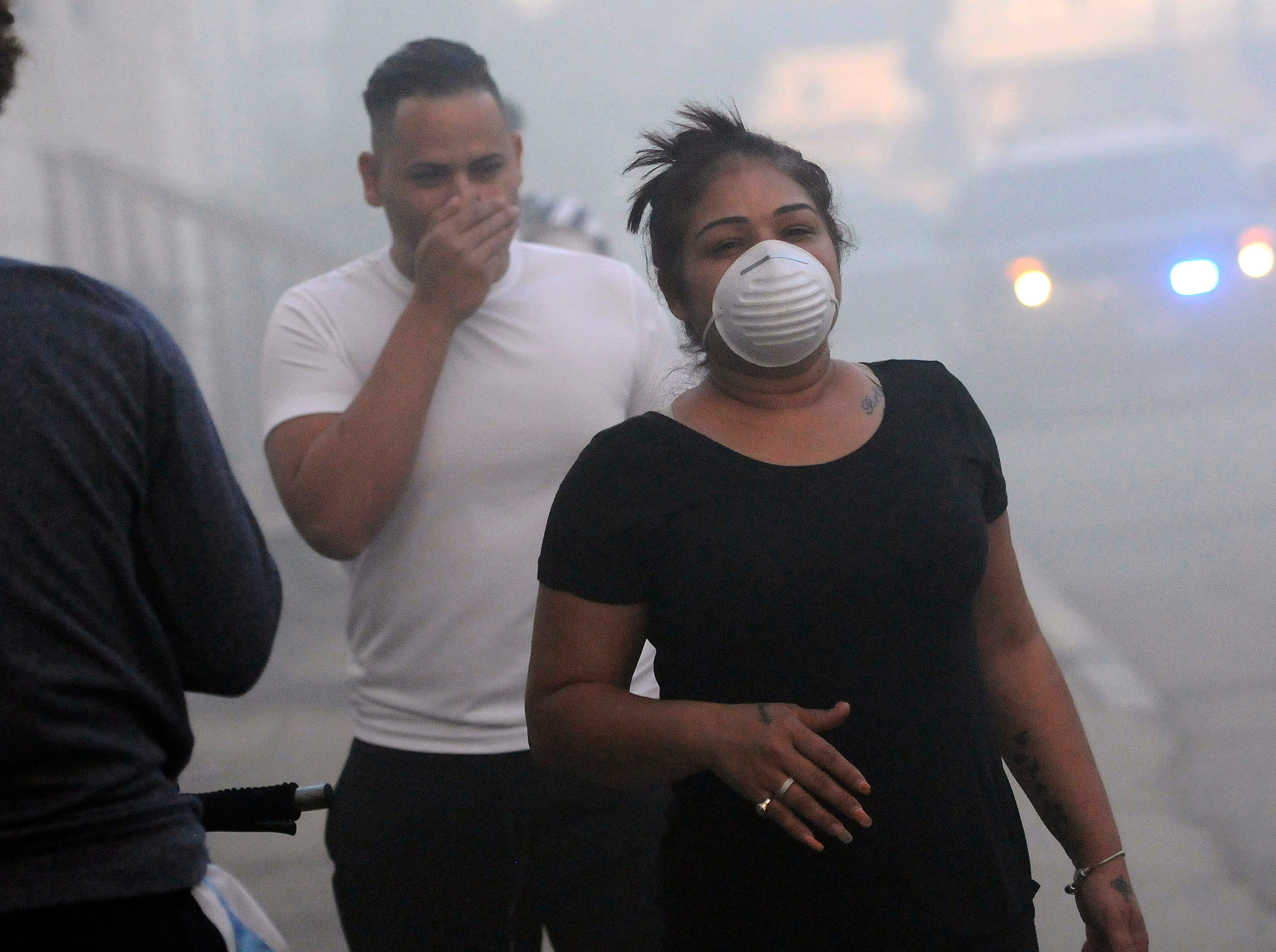 Residents cover their face from the smoke while being evacuated from homes as firefighters battle a fire on Bowdoin St., Thursday, Sept. 13, 2018 in Lawrence., Mass. A problem with a gas line that feeds homes in several communities north of Boston triggered a series of gas explosions and fires.