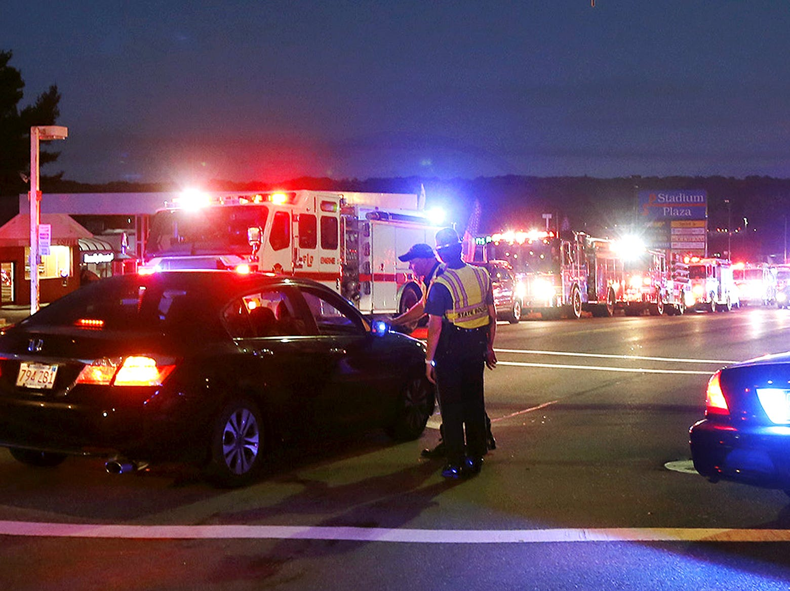 Police officers man a checkpoint as multiple fire trucks from surrounding communities are staged along a road Thursday, Sept. 13, 2018, in Lawrence, Mass. A problem with a gas line that feeds homes in several communities north of Boston triggered a series of gas explosions and fires.