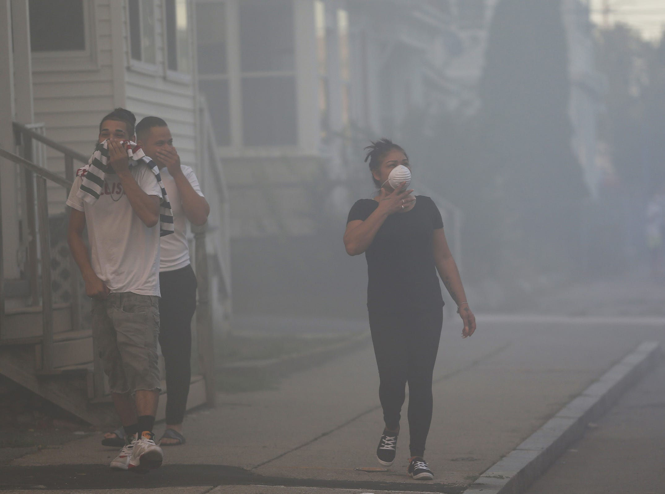People cover their faces to protect themselves from heavy smoke from a fire on Bowdoin Street in Lawrence, Mass., Thursday, Sept. 13, 2018. The company that owns Columbia Gas says its crews are performing safety checks after a series of fires and explosions erupted in three communities north of Boston.