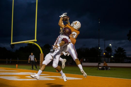 Beeville's Donyvan Givens catches a touchdown pass against a Tuloso-Midway defender during their game on Thursday, Sep. 14, 2018, at Veterans Memorial Stadium in Beeville.