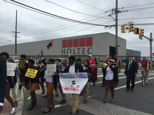 Protesters march outside Holtec headquarters in South Camden.