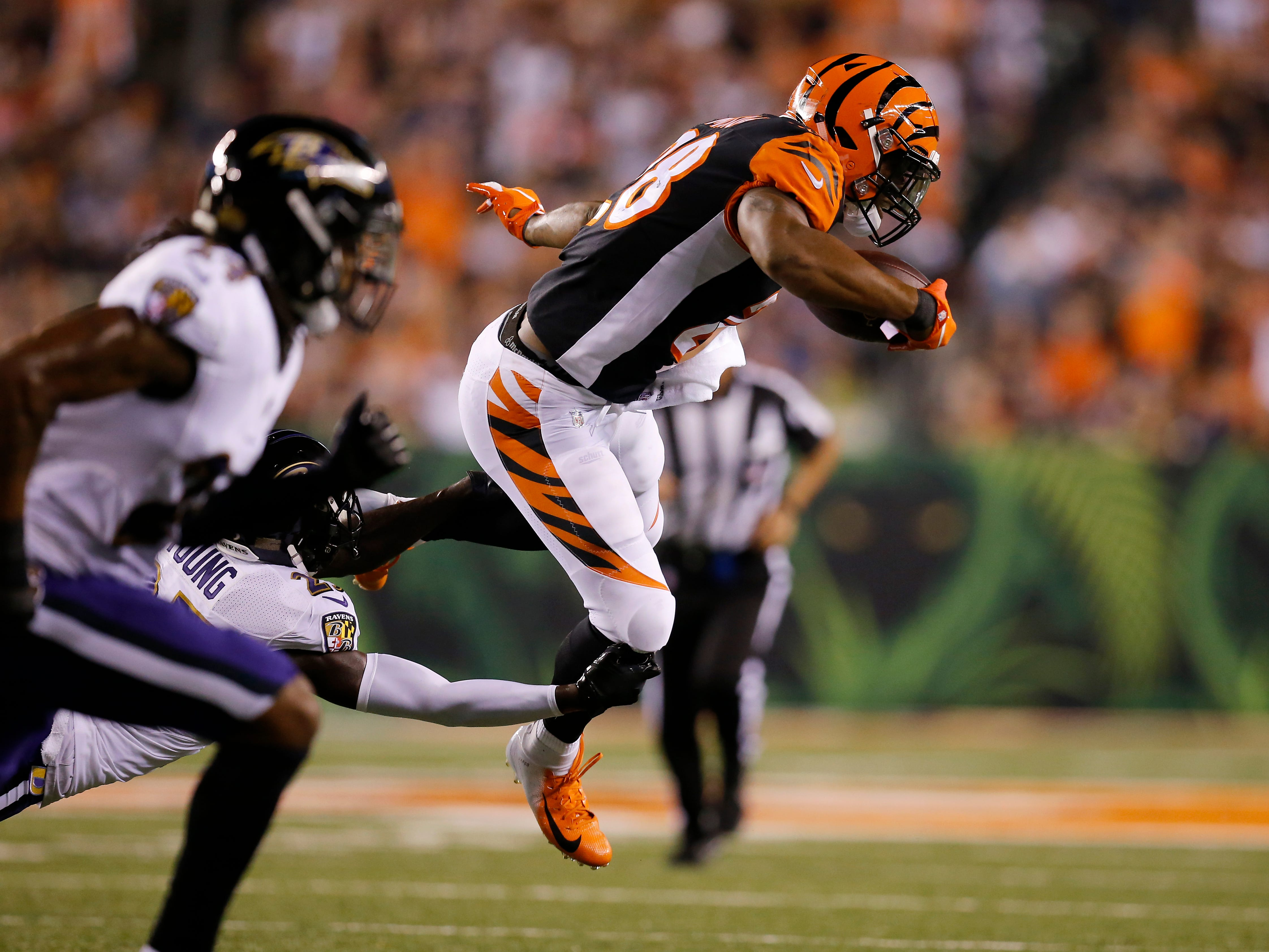 Cincinnati Bengals running back Joe Mixon (28) is tripped up leaping from a tackle in the first quarter of the NFL Week 2 game between the Cincinnati Bengals and the Baltimore Ravens at Paul Brown Stadium in downtown Cincinnati on Thursday, Sept. 13, 2018. The Bengals led 28-14 at halftime.