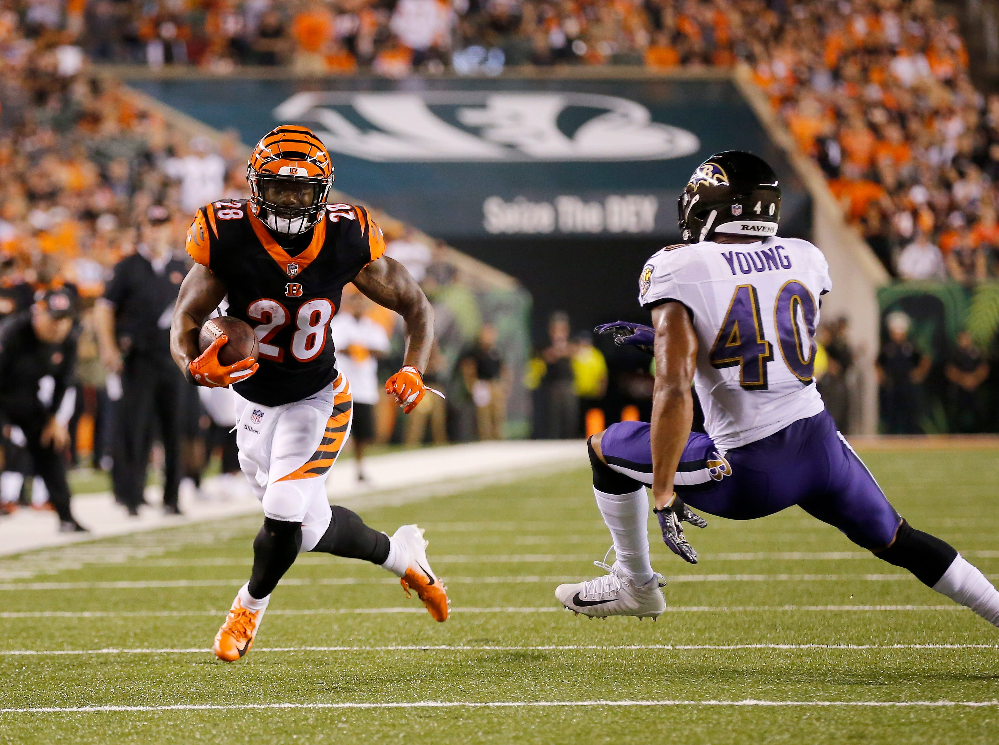 Cincinnati Bengals running back Joe Mixon (28) runs a catch past Baltimore Ravens linebacker Kenny Young (40) in the second quarter of the NFL Week 2 game between the Cincinnati Bengals and the Baltimore Ravens at Paul Brown Stadium in downtown Cincinnati on Thursday, Sept. 13, 2018. The Bengals led 28-14 at halftime.