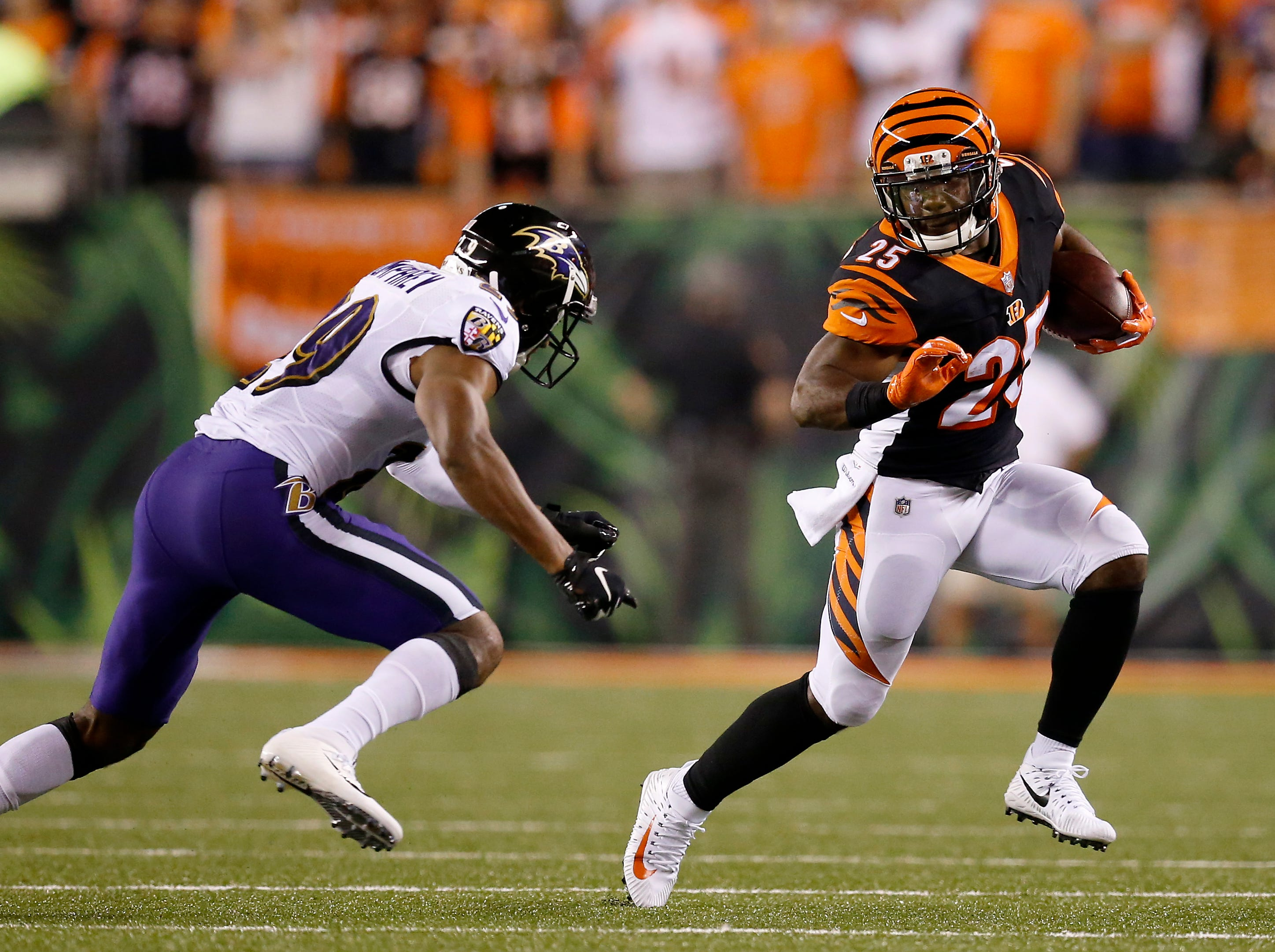 Cincinnati Bengals running back Giovani Bernard (25) runs from a tackle by Baltimore Ravens cornerback Marlon Humphrey (29) in the first quarter of the NFL Week 2 game between the Cincinnati Bengals and the Baltimore Ravens at Paul Brown Stadium in downtown Cincinnati on Thursday, Sept. 13, 2018. The Bengals led 28-14 at halftime.
