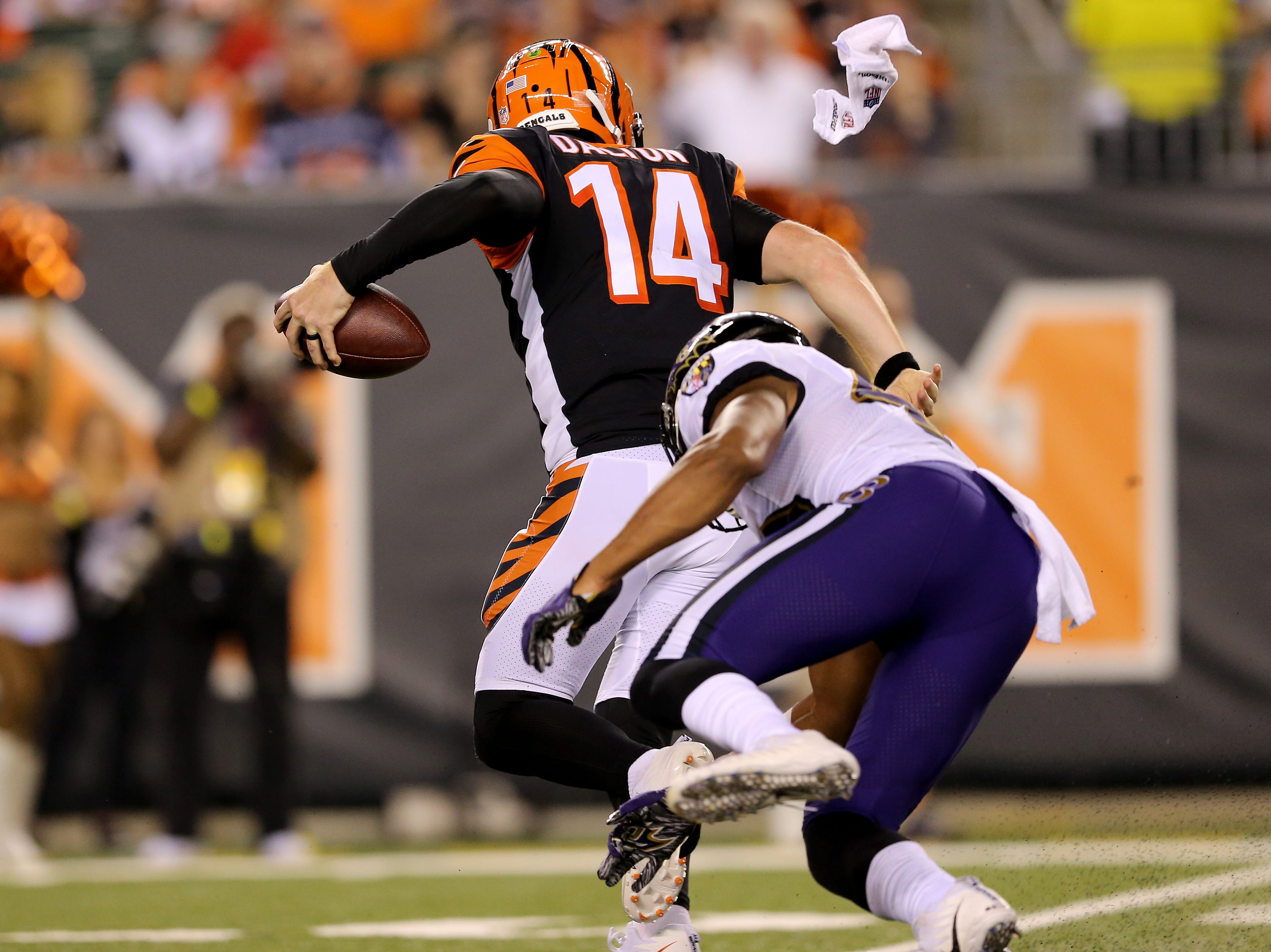 Cincinnati Bengals quarterback Andy Dalton (14) escapes pressure in the third quarter during the Week 2 NFL football game between the Baltimore Ravens and the Cincinnati Bengals, Friday, Sept. 14, 2018, Paul Brown Stadium in Cincinnati. Cincinnati won 34-23.
