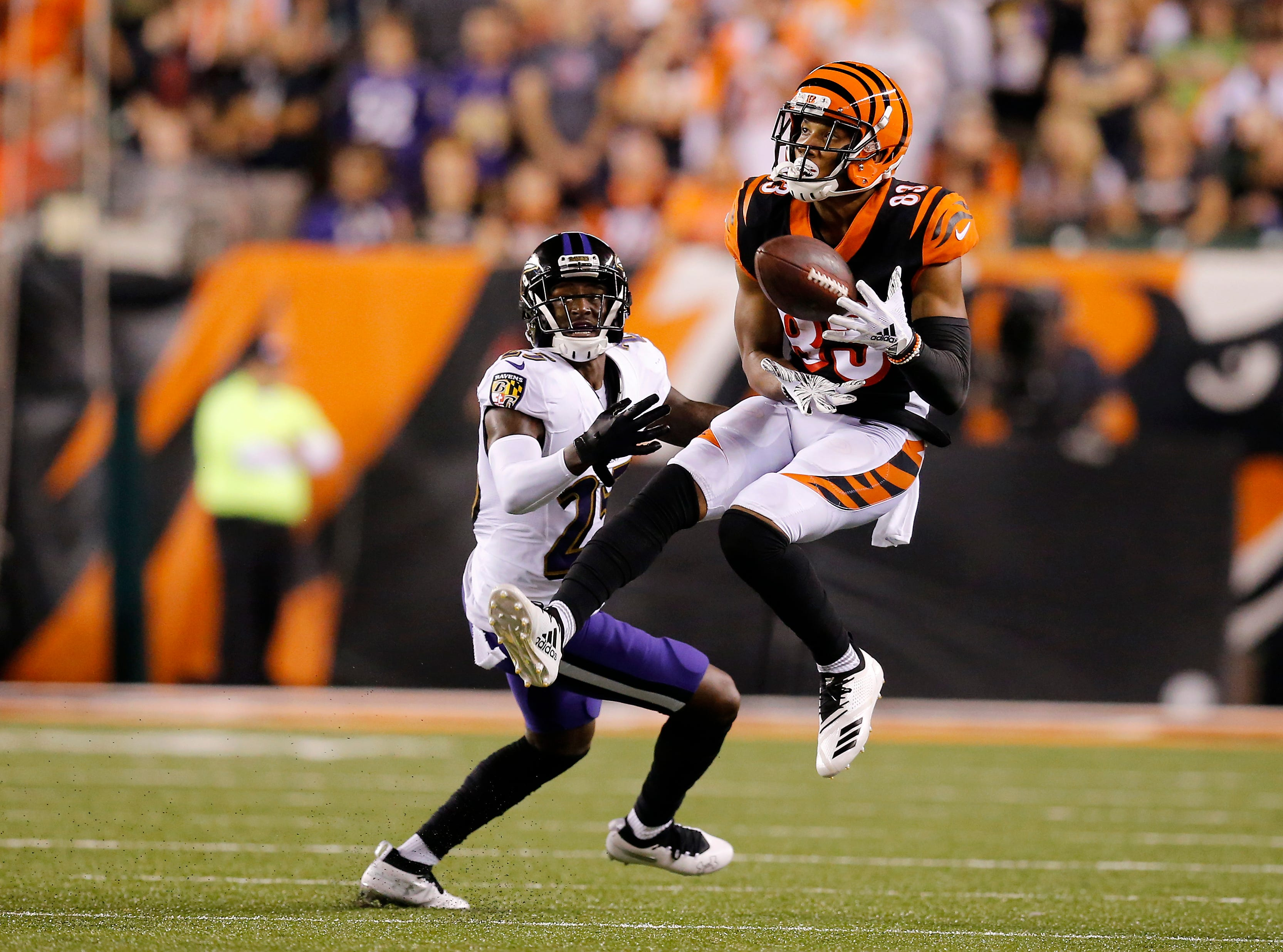 Cincinnati Bengals wide receiver Tyler Boyd (83) comes down with a catch ahead of Baltimore Ravens cornerback Tavon Young (25) in the second quarter of the NFL Week 2 game between the Cincinnati Bengals and the Baltimore Ravens at Paul Brown Stadium in downtown Cincinnati on Thursday, Sept. 13, 2018. The Bengals led 28-14 at halftime.
