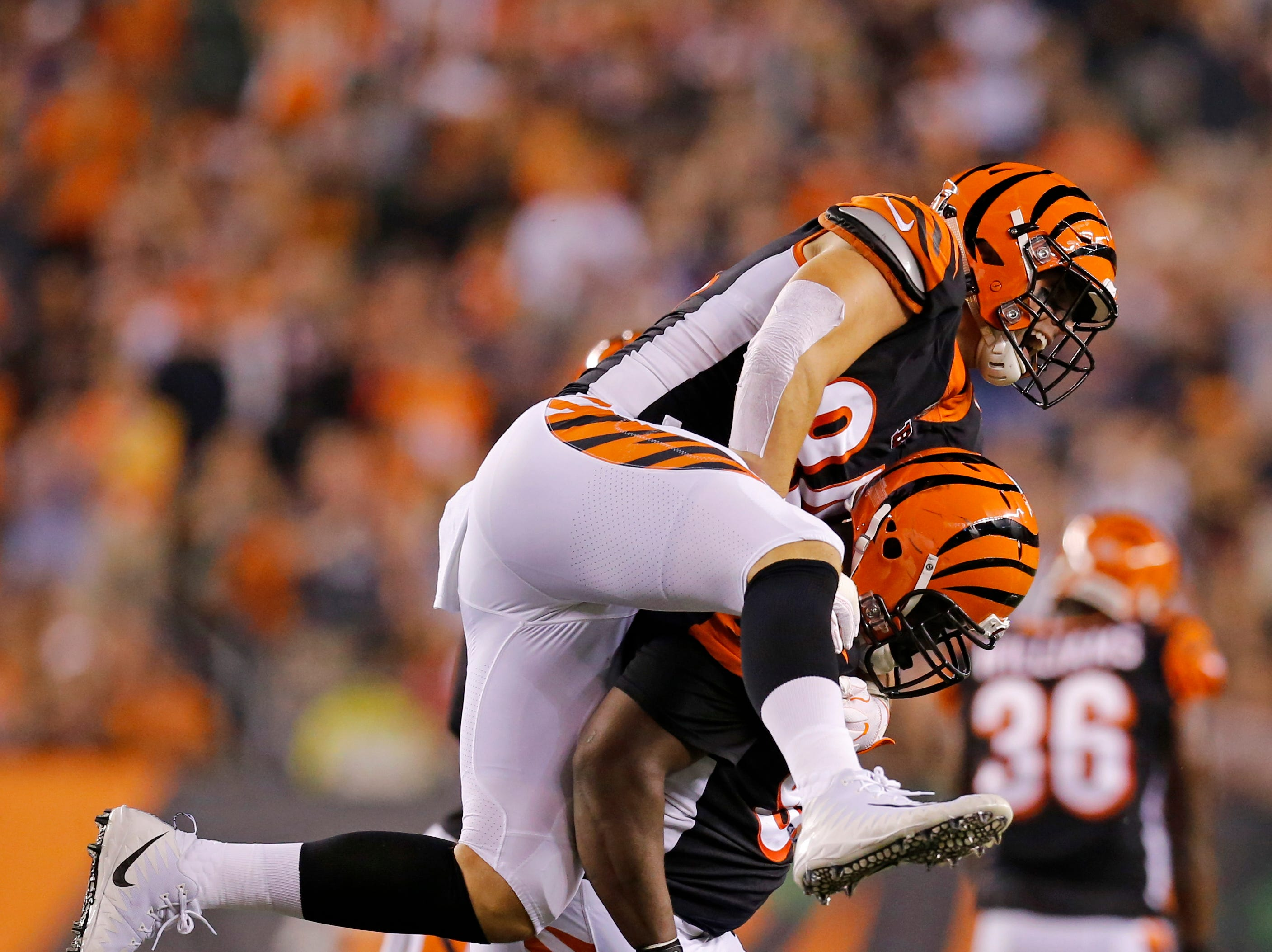 Cincinnati Bengals defensive end Sam Hubbard (94) jumps on the back of defensive tackle Geno Atkins (97) after a sack in the first quarter of the NFL Week 2 game between the Cincinnati Bengals and the Baltimore Ravens at Paul Brown Stadium in downtown Cincinnati on Thursday, Sept. 13, 2018. The Bengals led 28-14 at halftime.