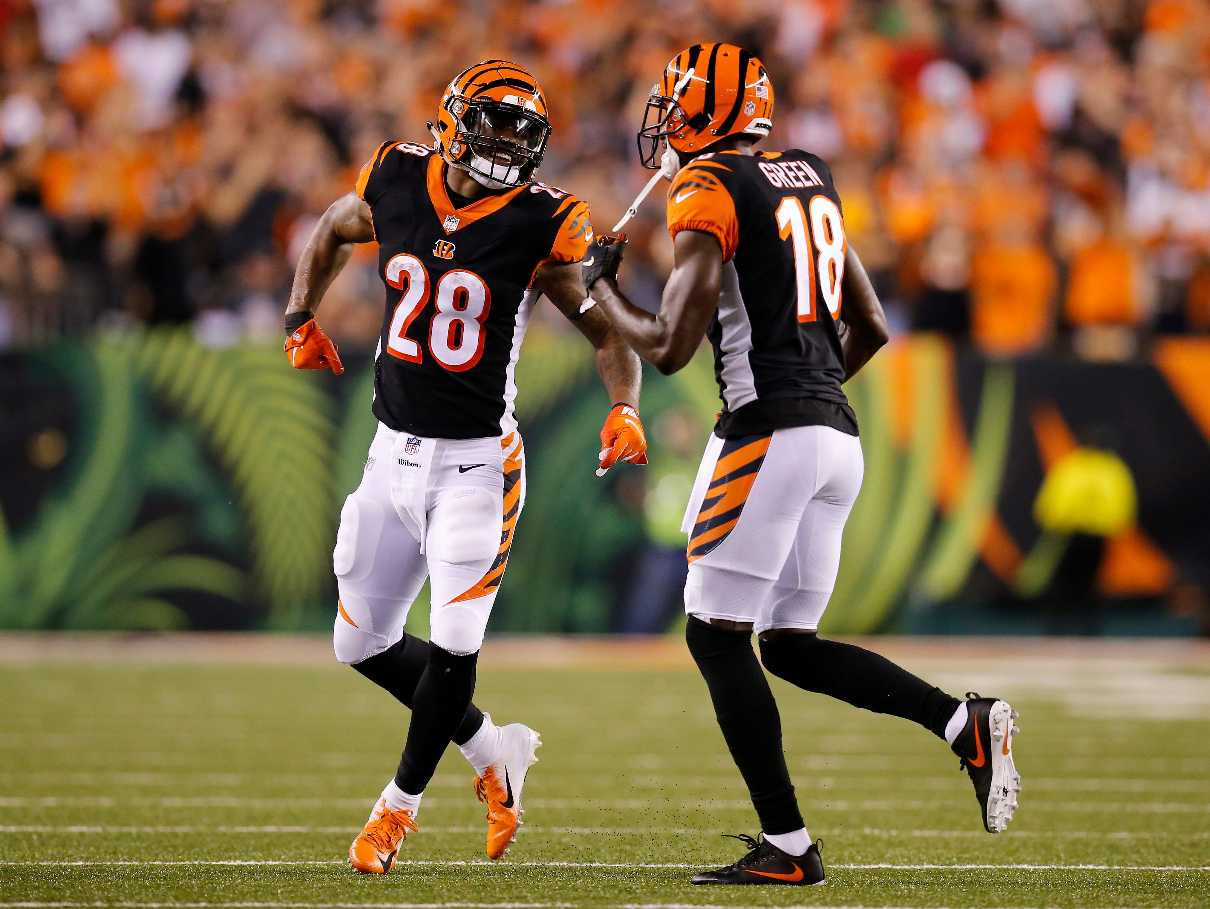 Cincinnati Bengals running back Joe Mixon (28) celebrates with wide receiver A.J. Green (18) after Green's third touchdown of the game in the second quarter of the NFL Week 2 game between the Cincinnati Bengals and the Baltimore Ravens at Paul Brown Stadium in downtown Cincinnati on Thursday, Sept. 13, 2018. The Bengals led 28-14 at halftime.