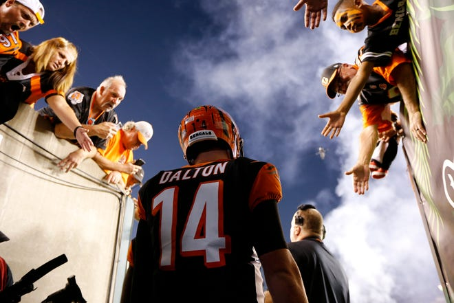 Fans reach out to Cincinnati Bengals quarterback Andy Dalton (14) before the first quarter of the NFL Week 2 game between the Cincinnati Bengals and the Baltimore Ravens at Paul Brown Stadium in downtown Cincinnati on Thursday, Sept. 13, 2018. The Bengals led 28-14 at halftime.