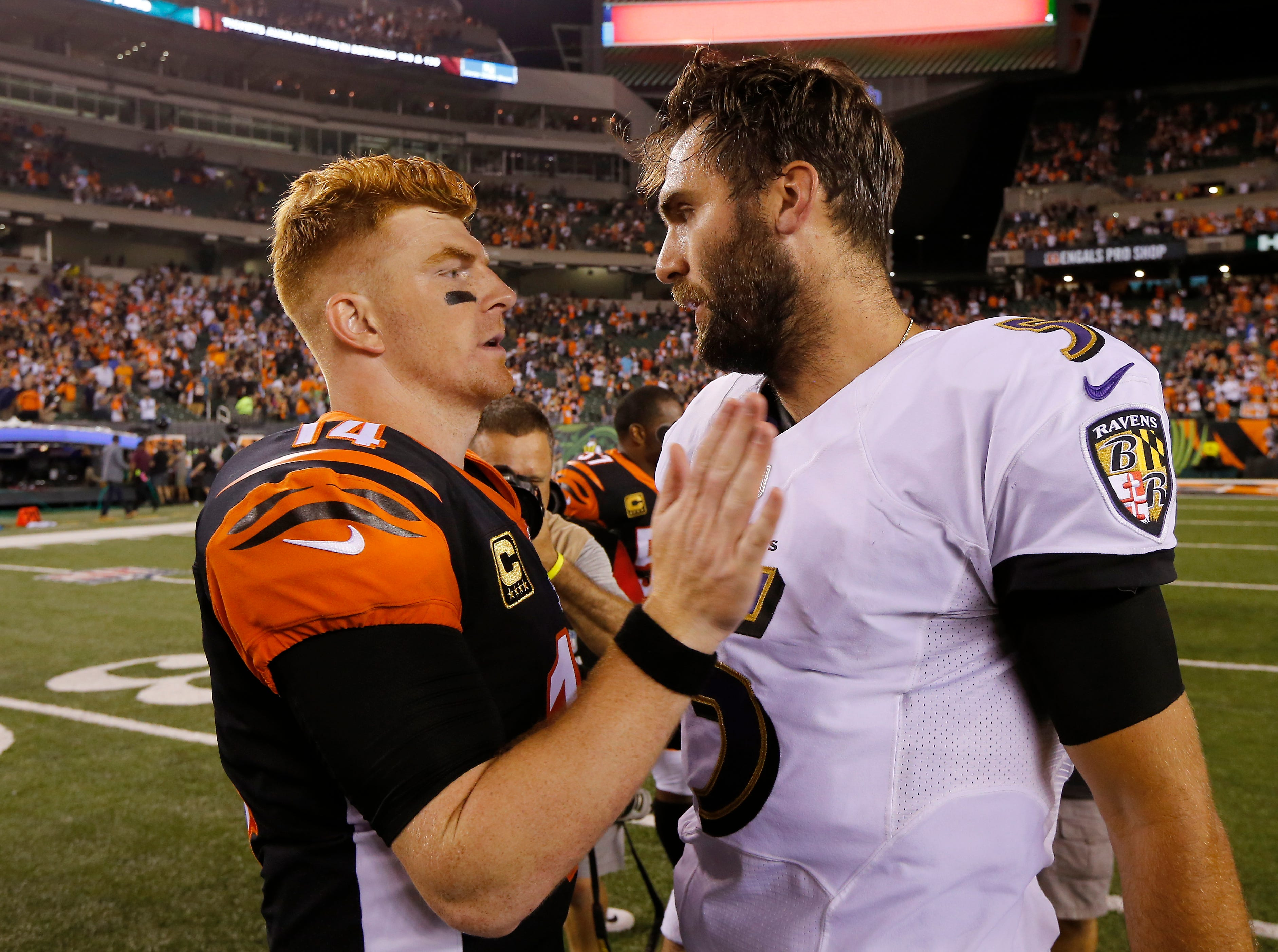 Cincinnati Bengals quarterback Andy Dalton (14) and Baltimore Ravens quarterback Joe Flacco (5) shake hands after the fourth quarter of the NFL Week 2 game between the Cincinnati Bengals and the Baltimore Ravens at Paul Brown Stadium in downtown Cincinnati on Thursday, Sept. 13, 2018. The Bengals improved to 2-0 on the season with a 34-23 win over the Ravens.