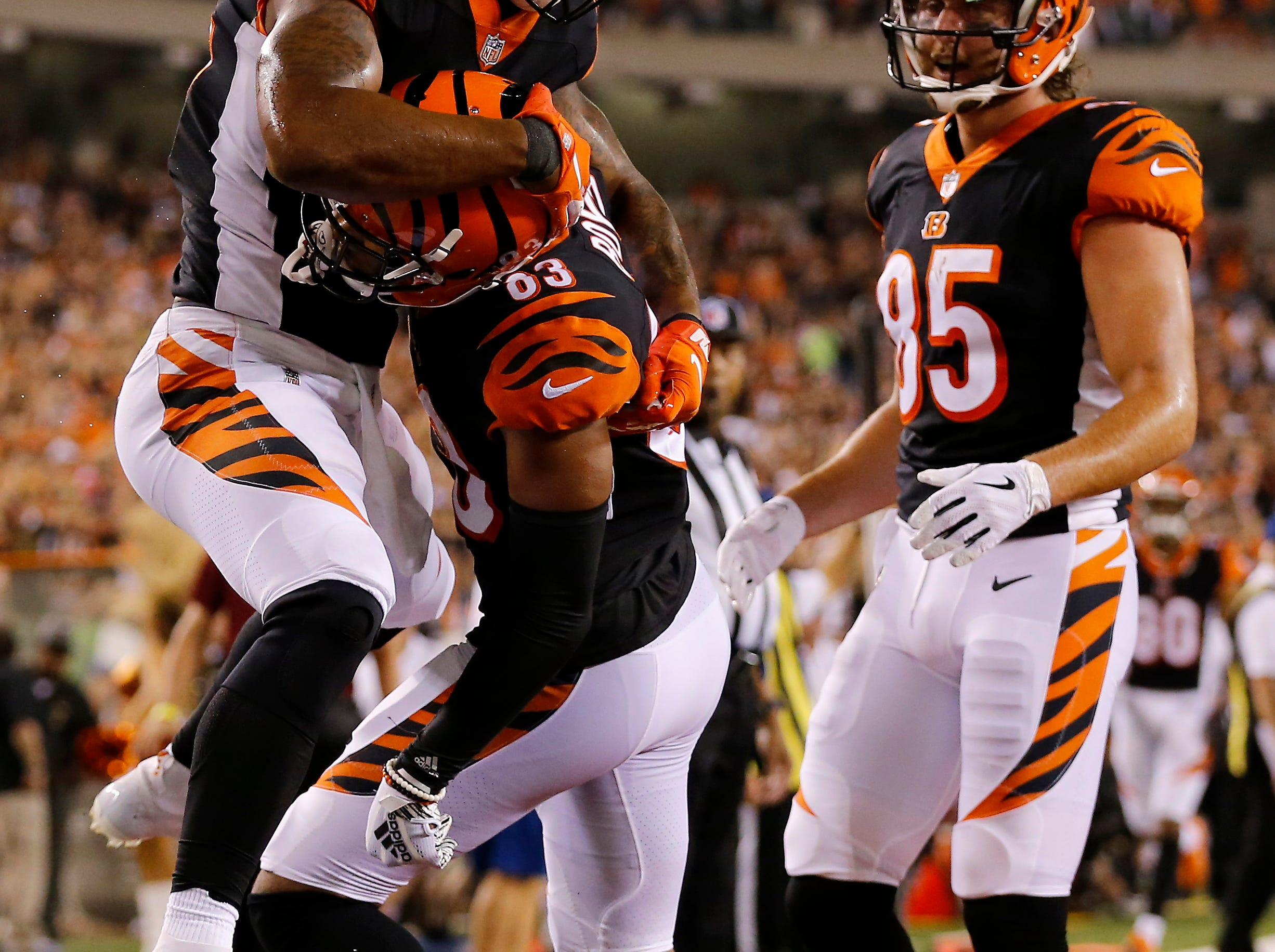 Cincinnati Bengals running back Joe Mixon (28) jumps on wide receiver Tyler Boyd (83) as they celebrate Boyd's touchdown in the second quarter of the NFL Week 2 game between the Cincinnati Bengals and the Baltimore Ravens at Paul Brown Stadium in downtown Cincinnati on Thursday, Sept. 13, 2018. The Bengals led 28-14 at halftime.