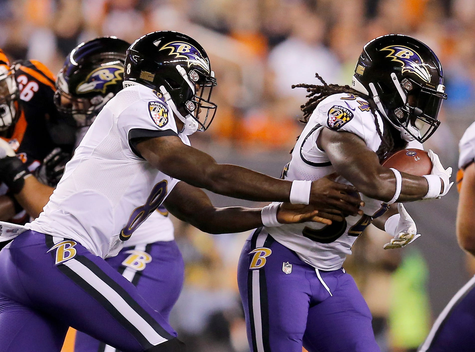 Baltimore Ravens quarterback Lamar Jackson (8) hands off to running back Alex Collins (34) in the first quarter of the NFL Week 2 game between the Cincinnati Bengals and the Baltimore Ravens at Paul Brown Stadium in downtown Cincinnati on Thursday, Sept. 13, 2018. The Bengals led 28-14 at halftime.